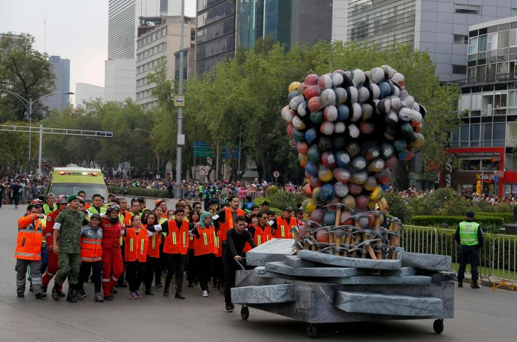 The giant statue of a fist was followed by brave volunteers who helped the earthquake rescue efforts