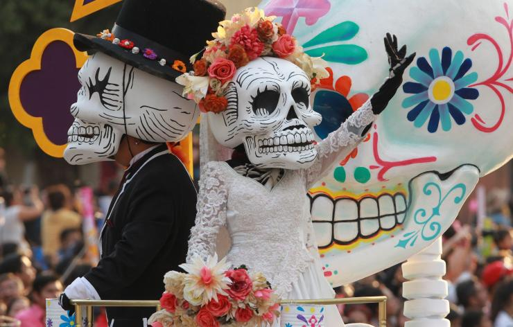 These skulls are dressed as bride and groom, waving at well-wishers as they parade down the street