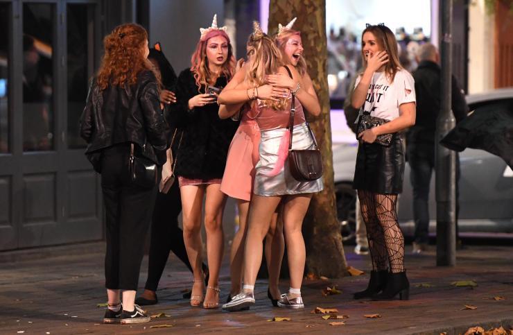 Girls dressed as unicorns smile as they hug on Saturday night