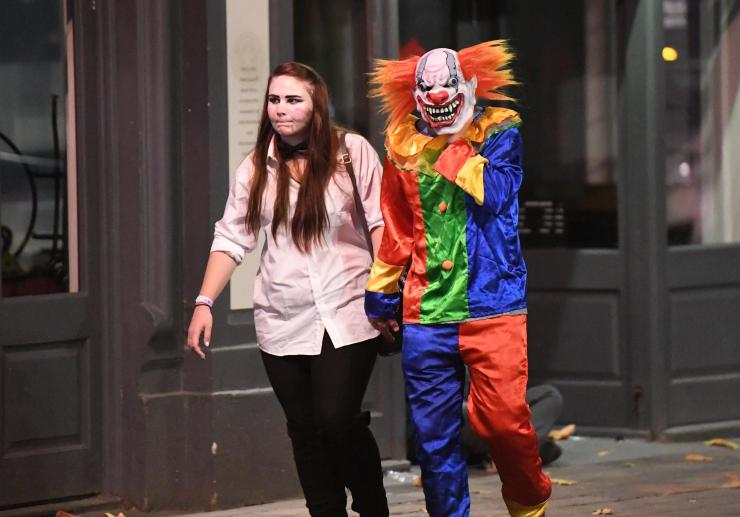 A terrifying clown holds hands with a ghoulish Halloween reveller