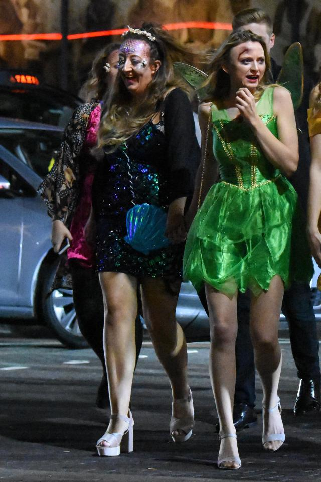 A Tinkerbell clasps hands with a friend as they walk down the street