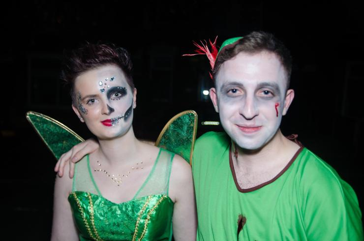 A dead Tinkerbell and Peter Pan smile in their impressive outfits
