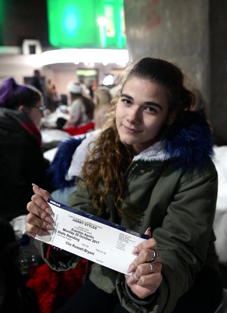 One fan proudly displays her ticket to Monday's concert, meaning she faces another night sleeping on the streets