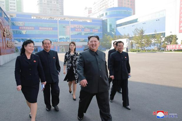 The dictator pictured with his wife outside the factory in the crackpot country