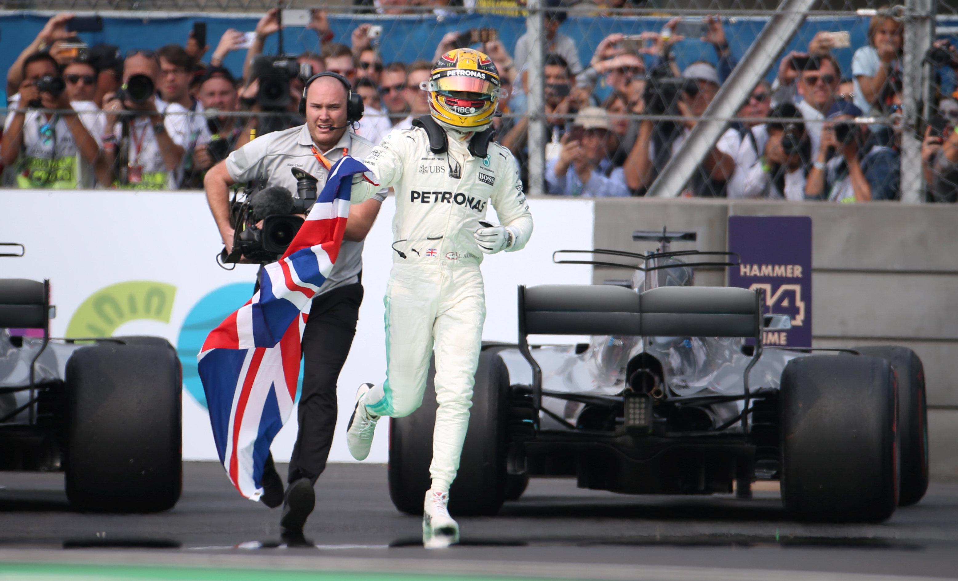 Lew races away from his car holding the Union Flag