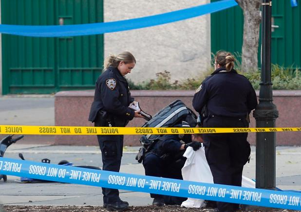 Cops stand over the body of a victim of the incident