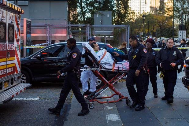 Emergency personnel carry a man into an ambulance after the atrocity