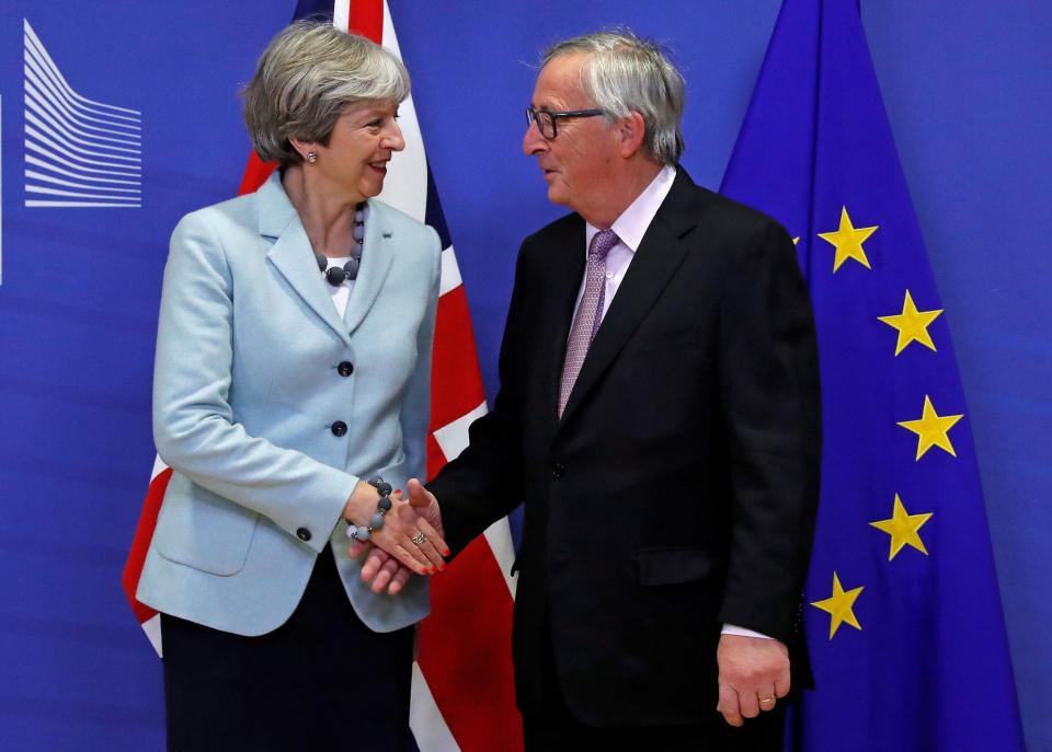 Theresa May and Jean-Claude Junker shake hands at EC headquarters