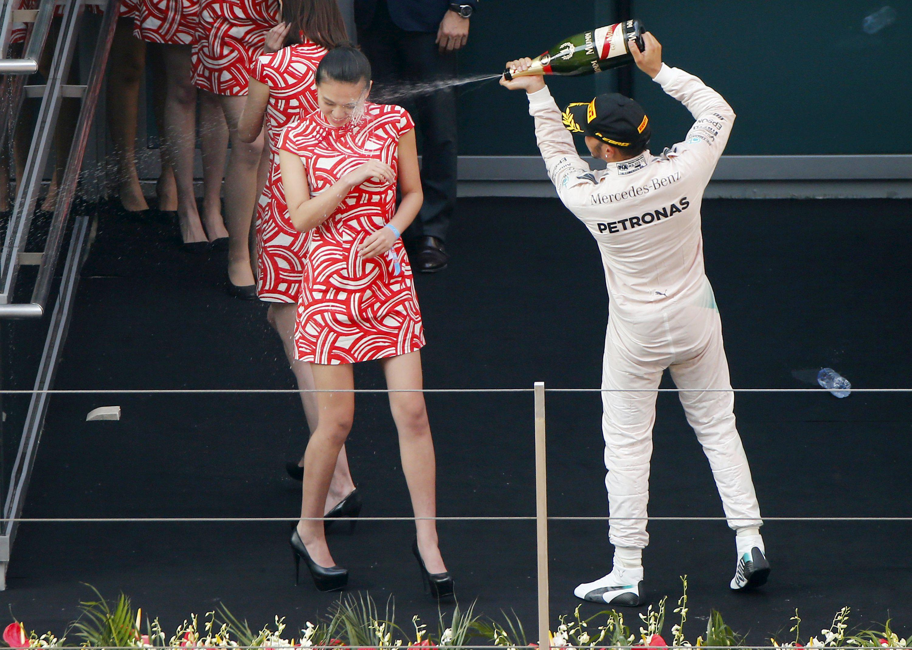 Lewis Hamilton drenches the pit girls in champagne on the podium