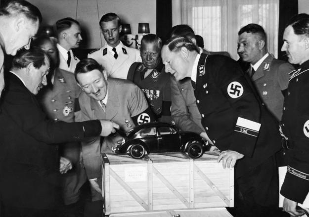 Adolf Hitler admires a model of the Volkswagen car along with the designer Ferdinand Porsche, left, pictured with his arm out stretched