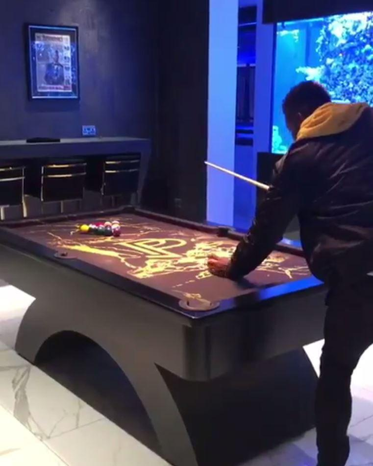 Paul Pogba looks relaxed as he plays billiards in his Cheshire mansion