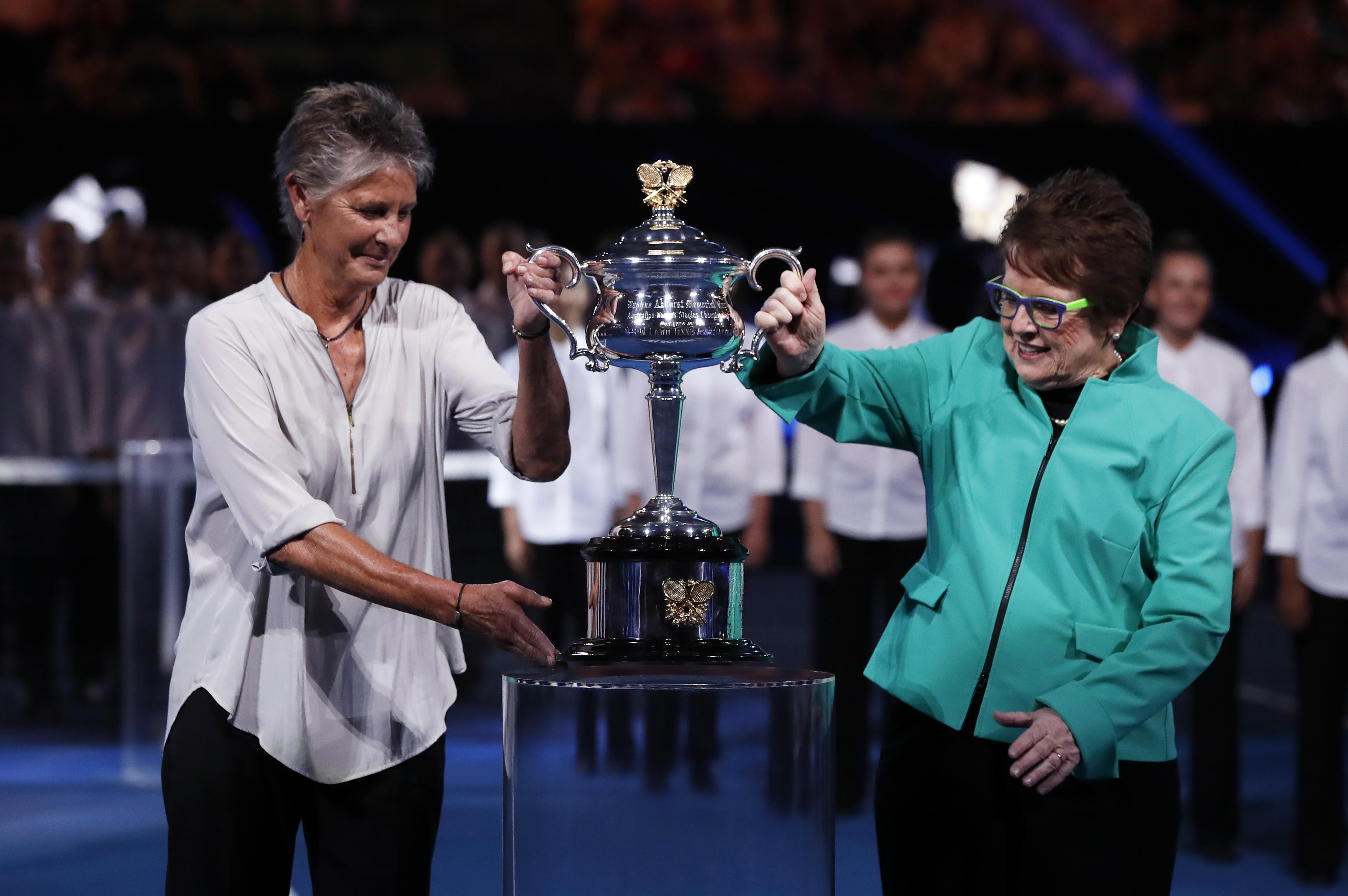 Chris O'Neil and Billie Jean King lift the trophy into place in Melbourne