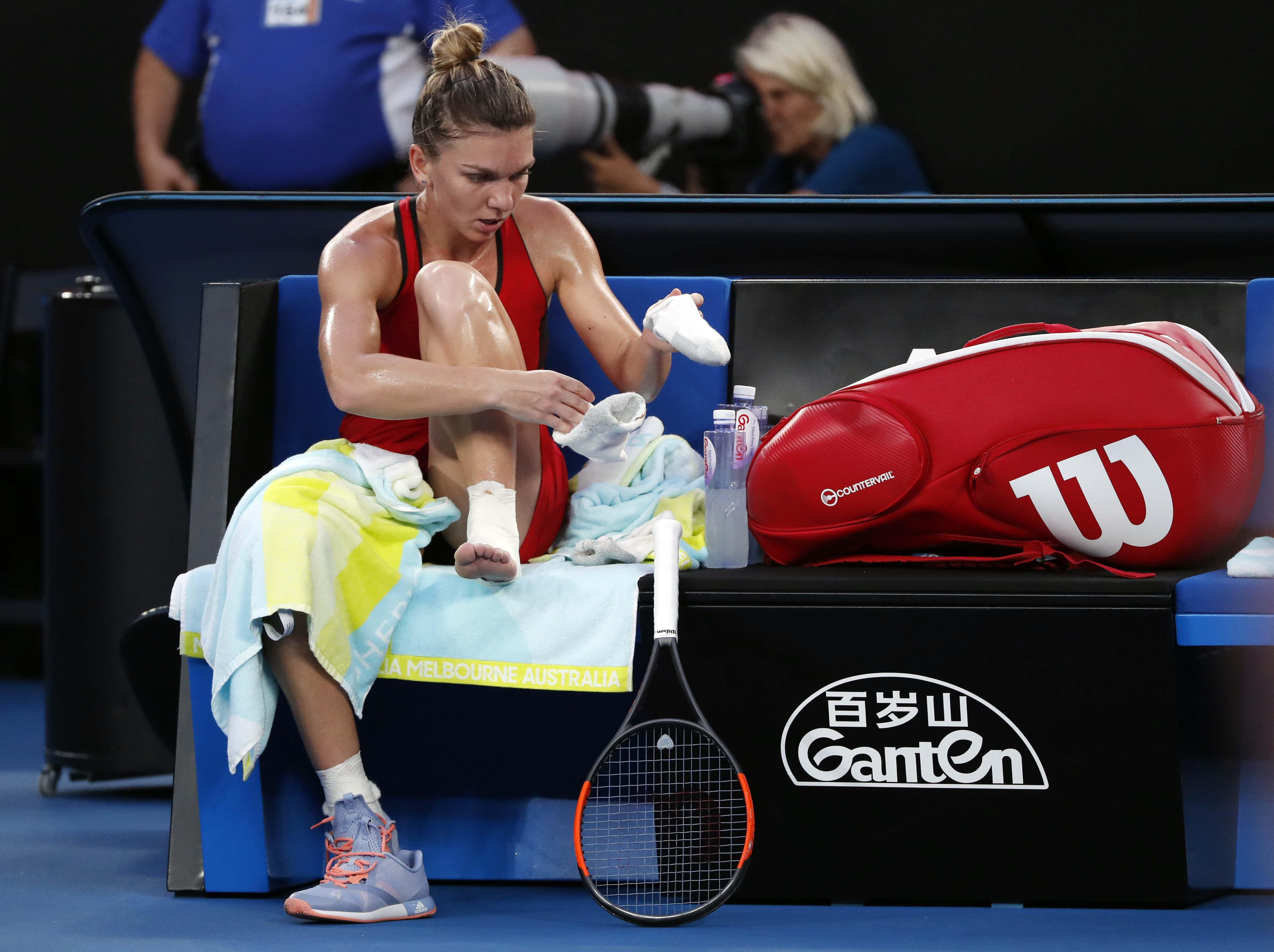 Halep readjusts her foot strapping during a break in play
