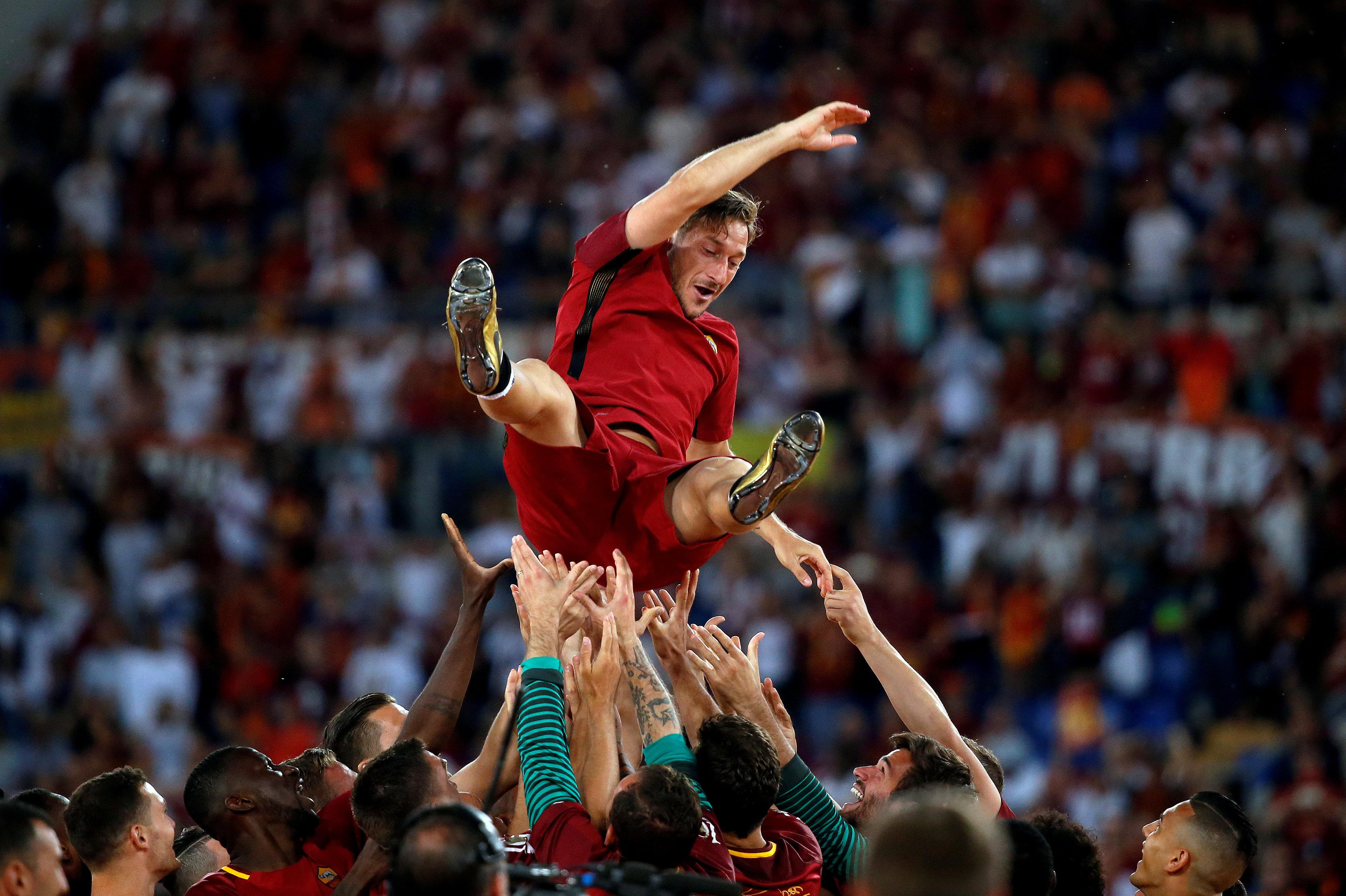 Francesco Totti is launched into the air by his Roma team-mates