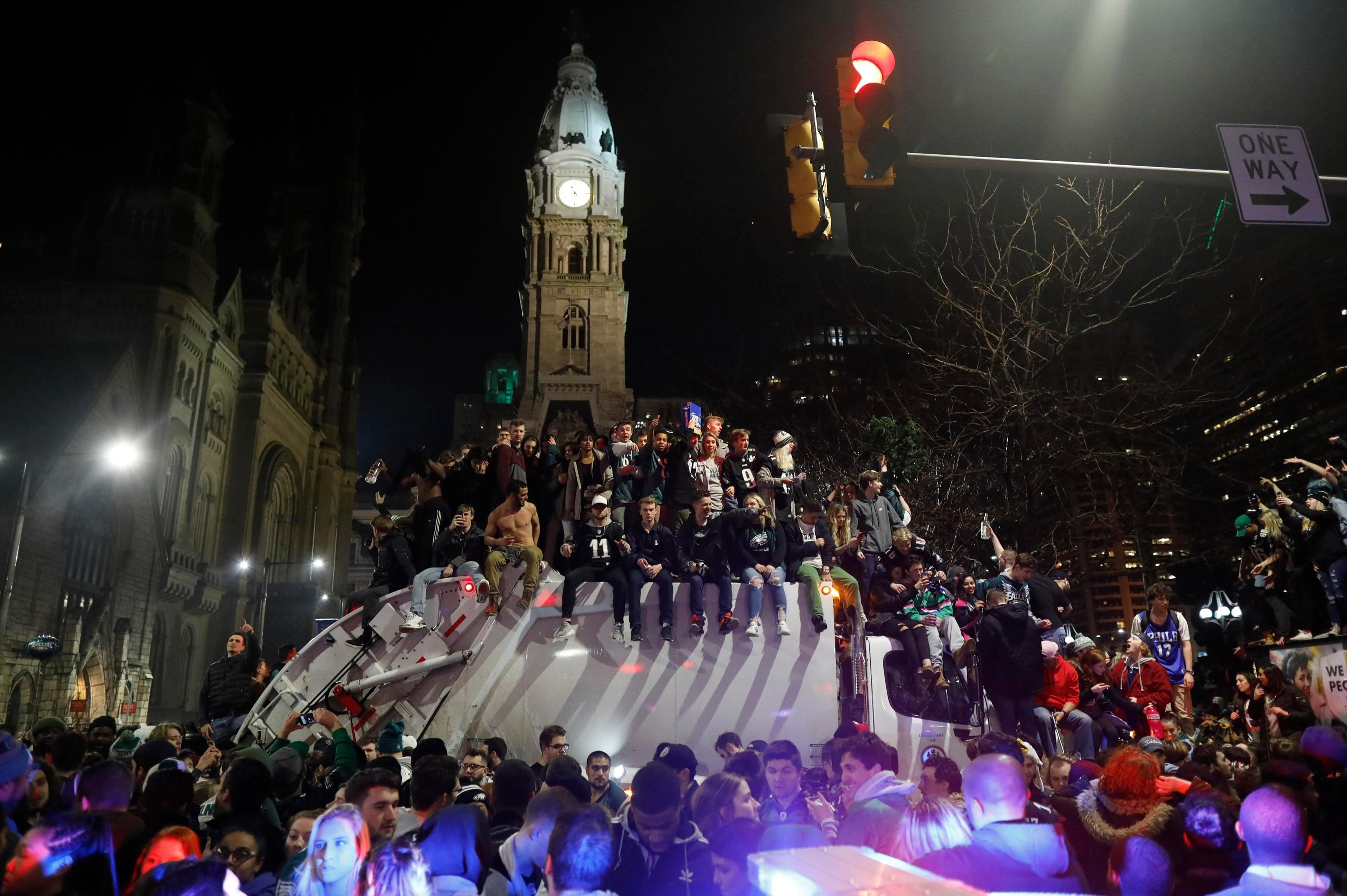 Dozens of revellers jumped on top of a rubbish truck as they partied on the streets
