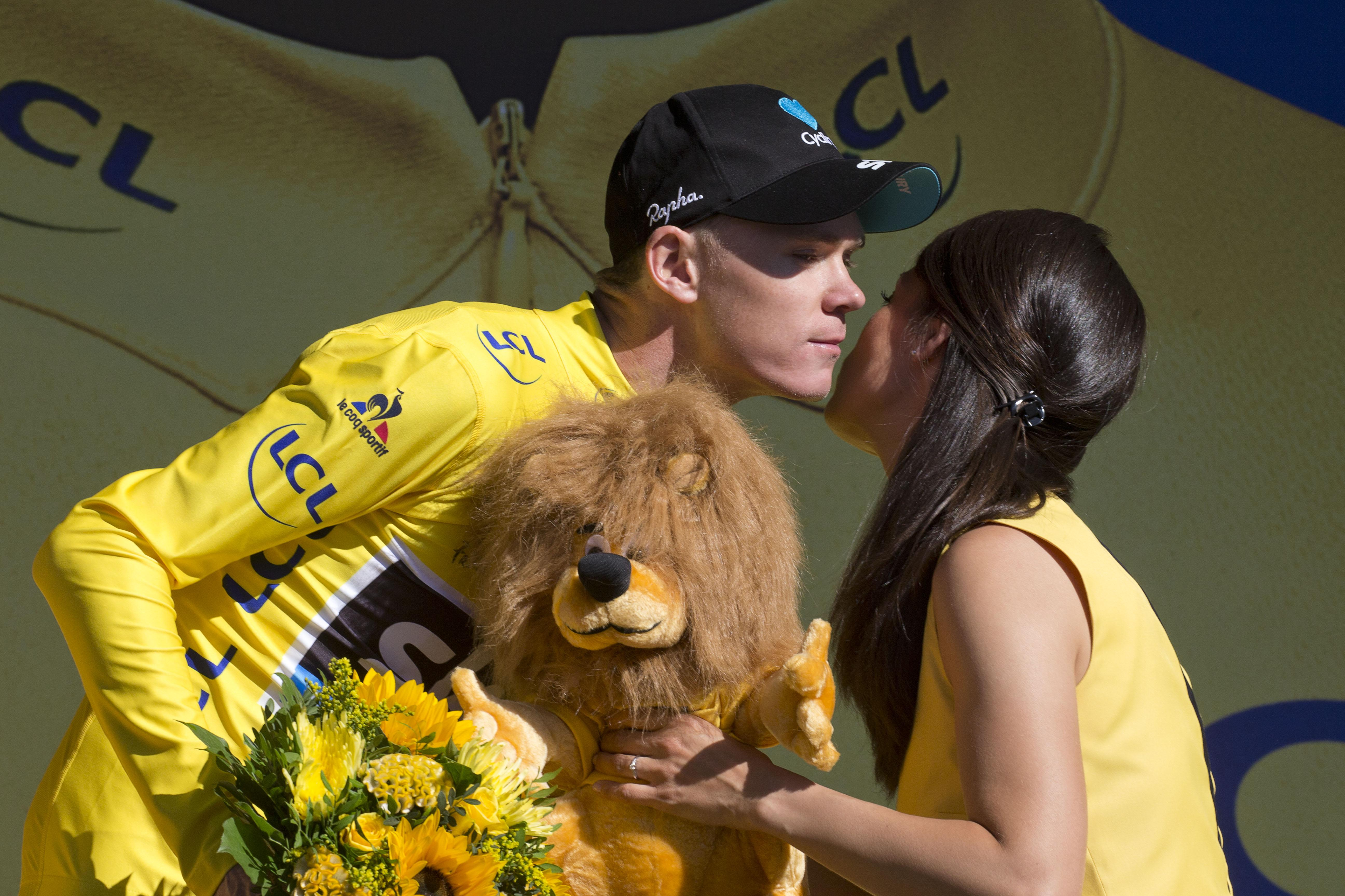 Chris Froome is greeted by a podiun girl last year