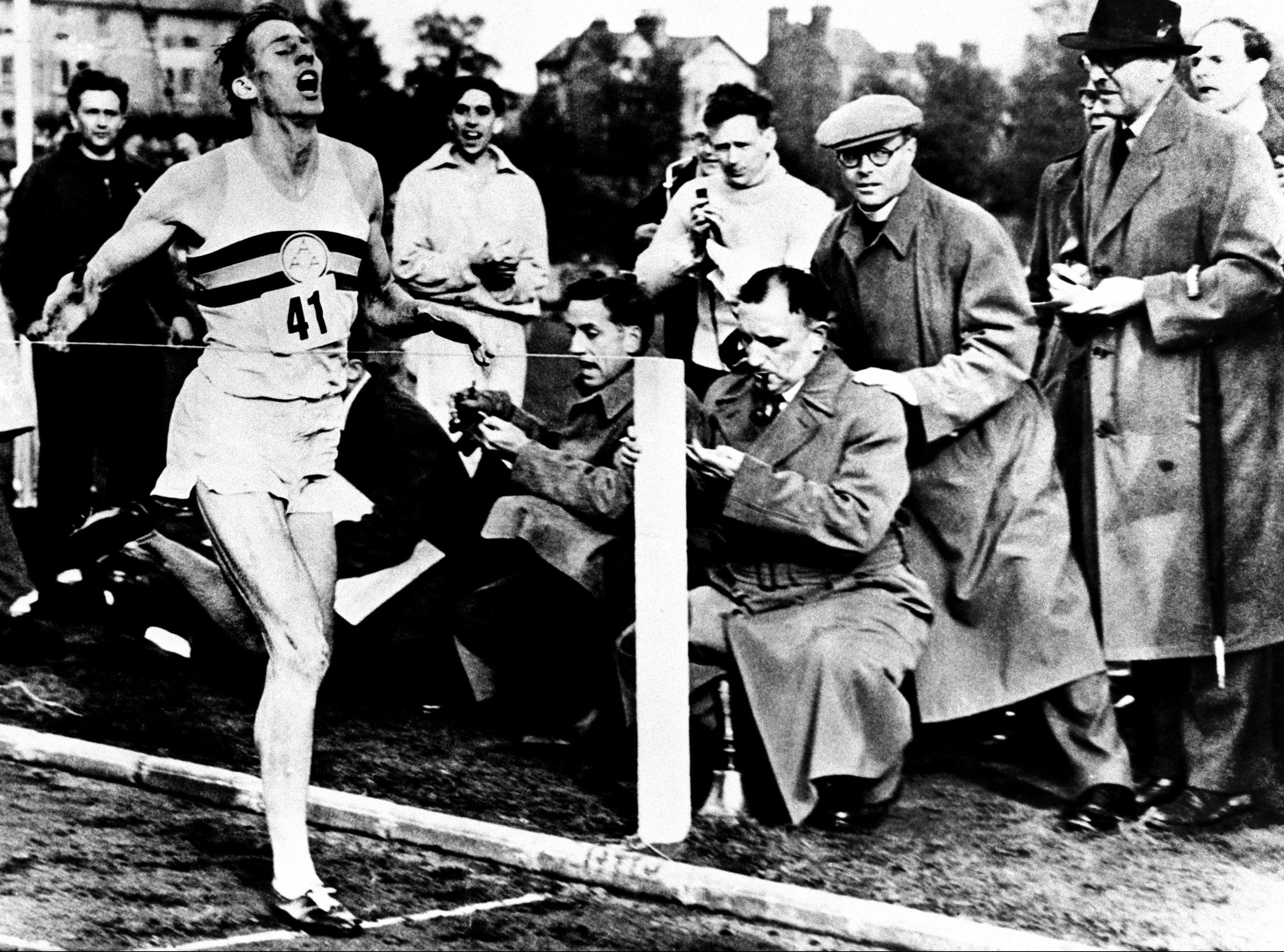 Roger Bannister hits the tape to register the first sub four-minute mile