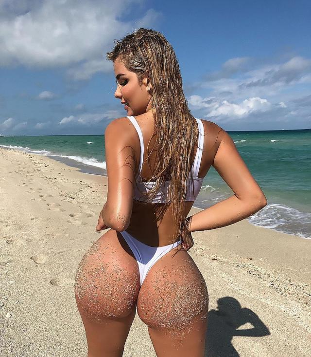 Anastasia poses for followers after sitting in the sand