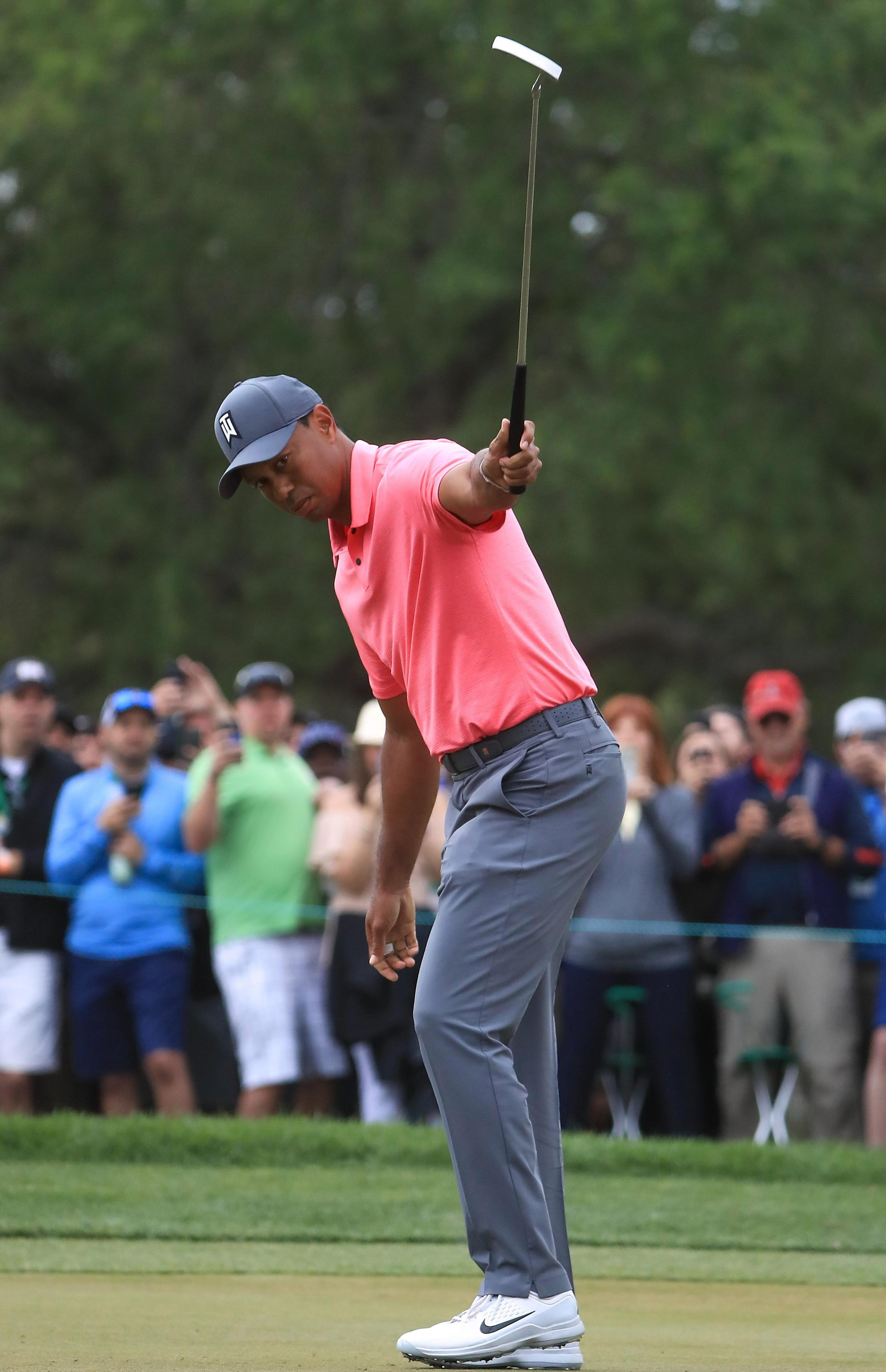 Tiger Woods rolled in a 20-foot birdie on the tenth to a chorus of roars