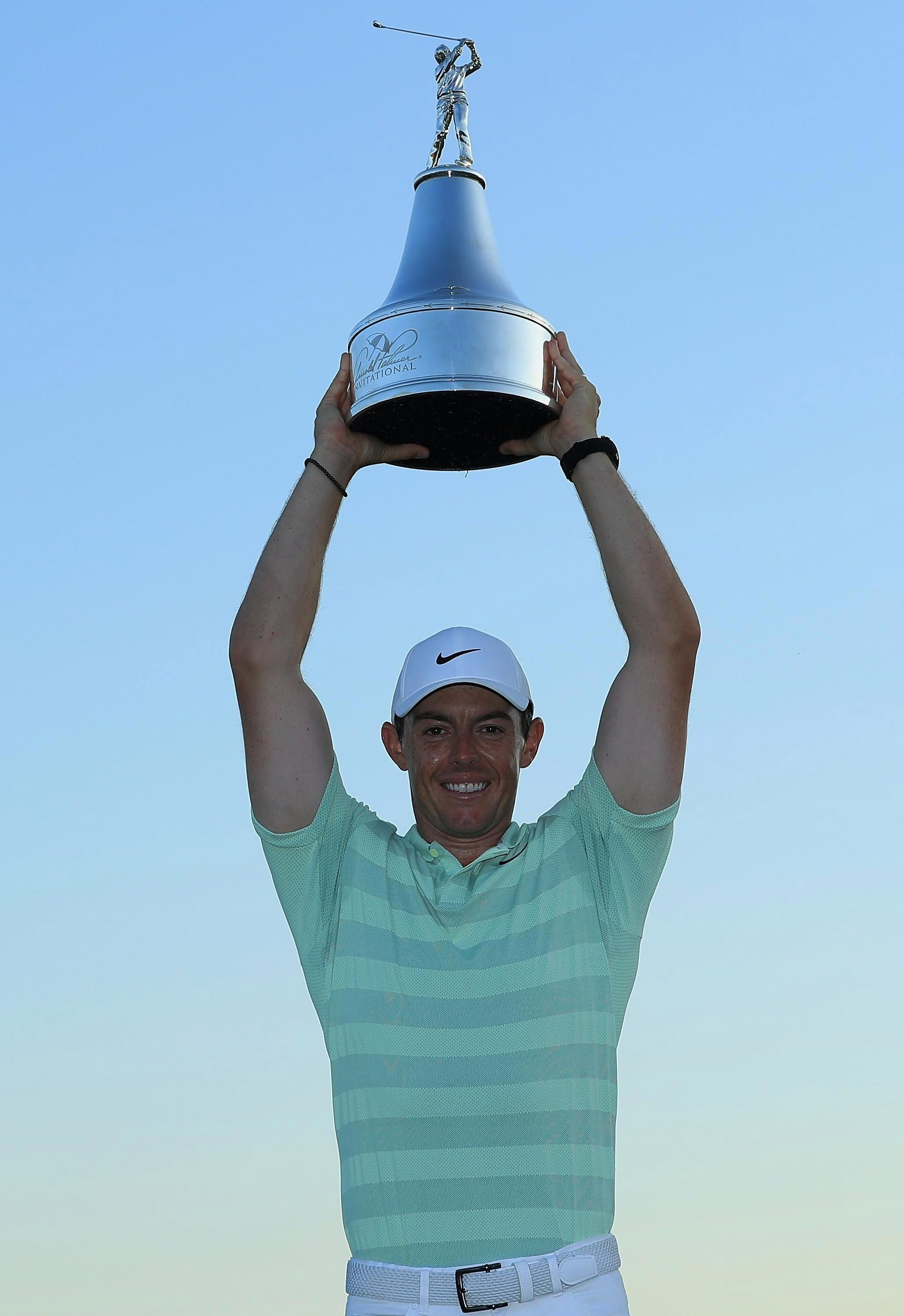 The four-time major winner holds the trophy aloft after his two-shot victory