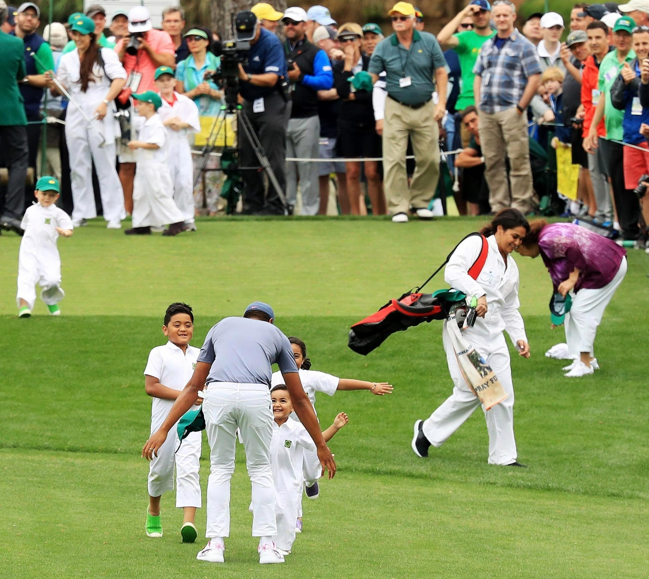 Somehow the golfer manages to walk back up the fairway to greet his family who had raced to join him in celebrating