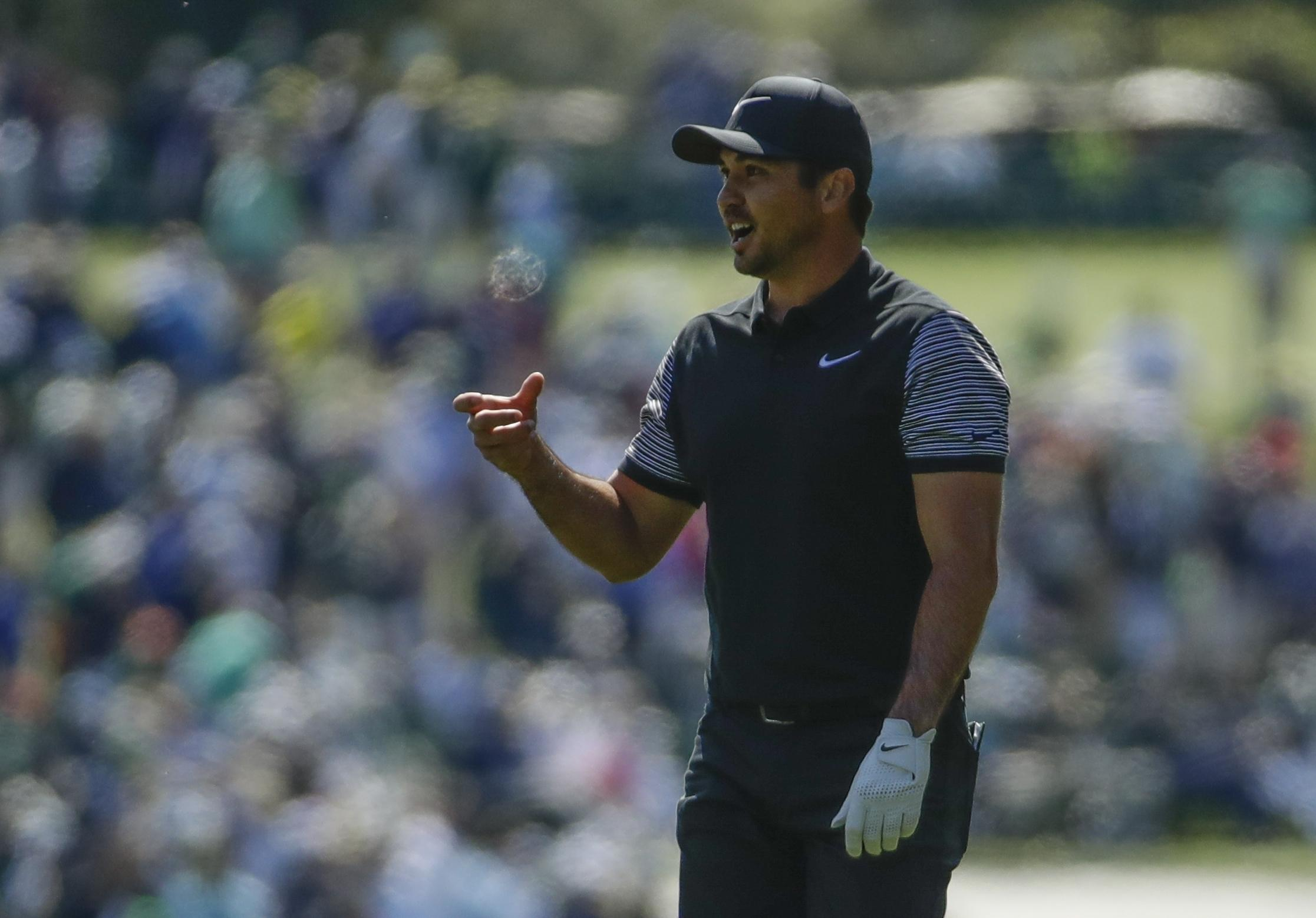 Jason Day looks shocked as he finds his ball has made its way to the bottom of the wrong cup