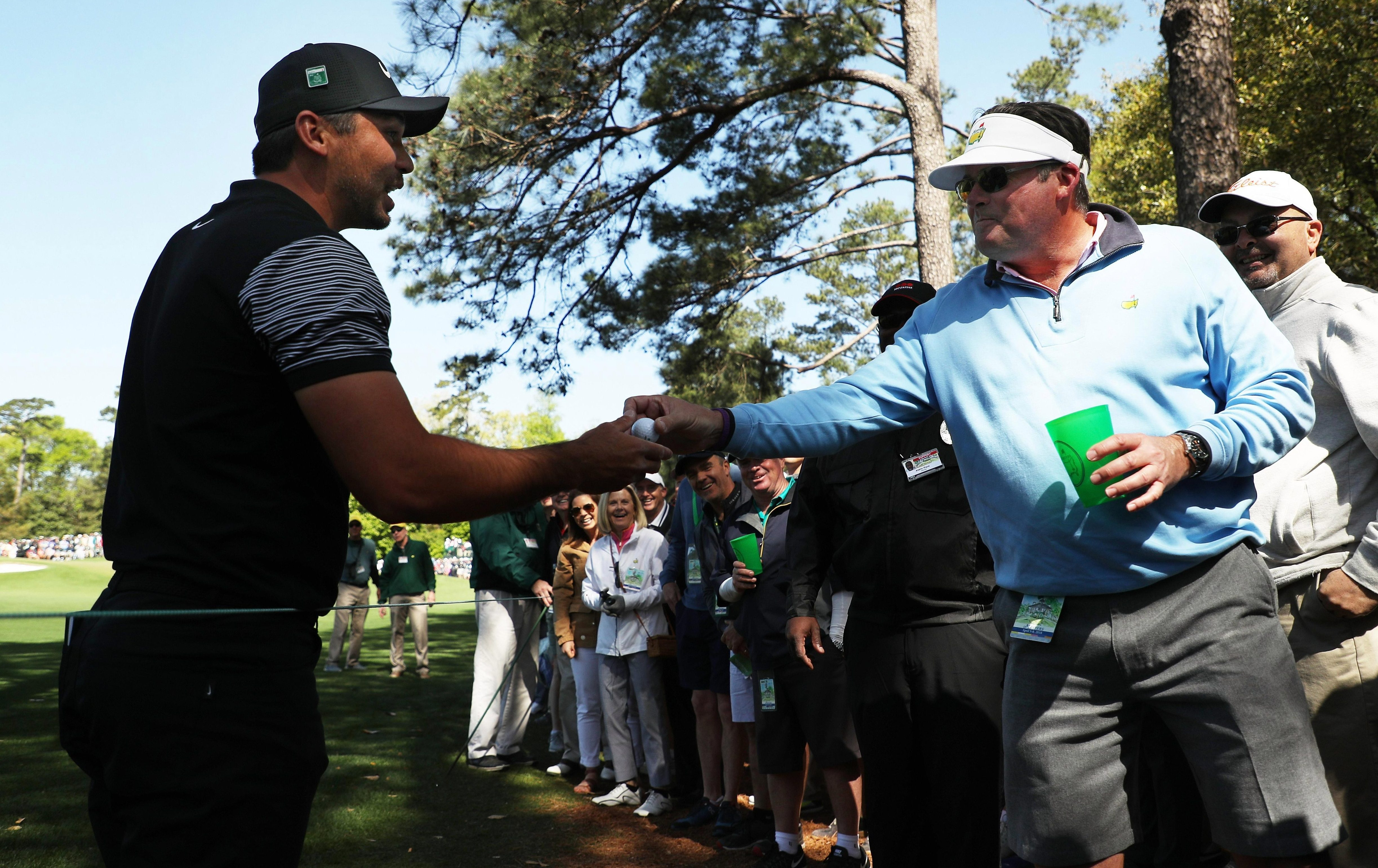 Jason Day gets his ball back after hitting into a fan's cup on the first hole