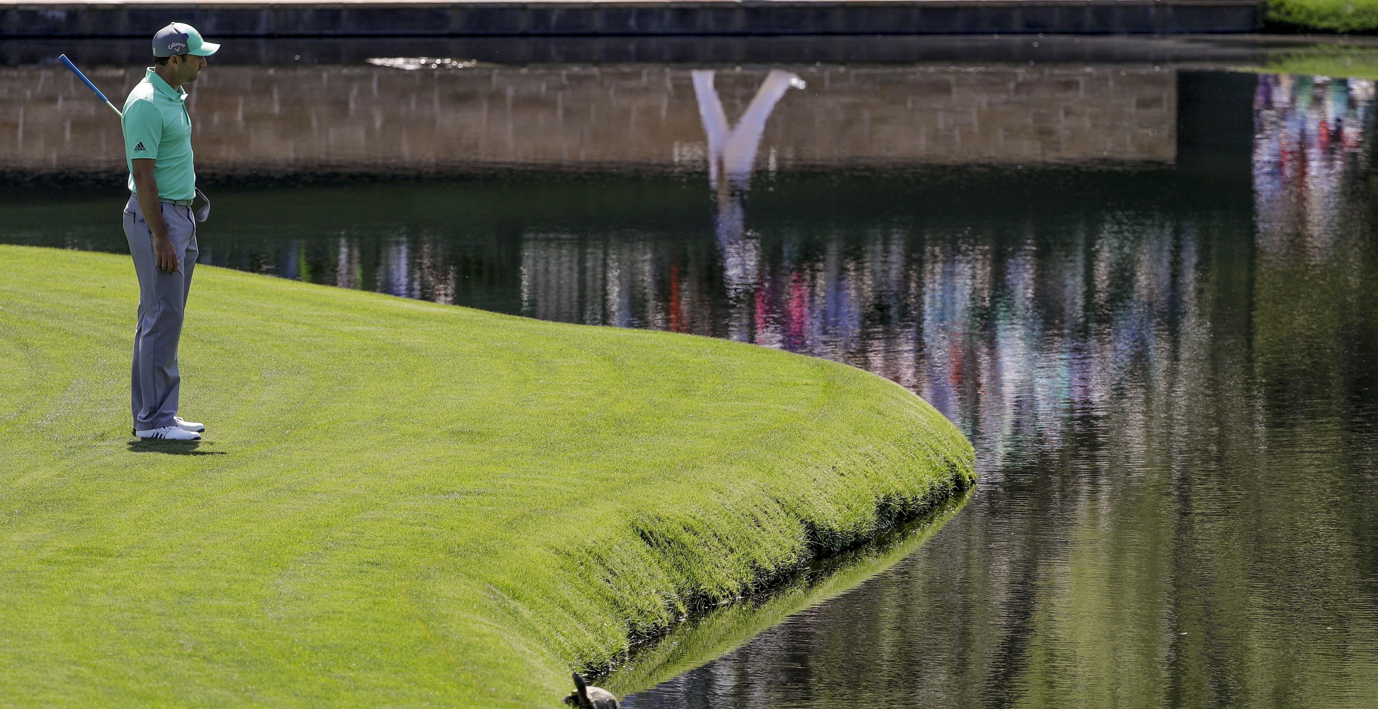 Garcia cannot believe it as he peers down into the water on the 15th as his Masters challenge went up in smoke