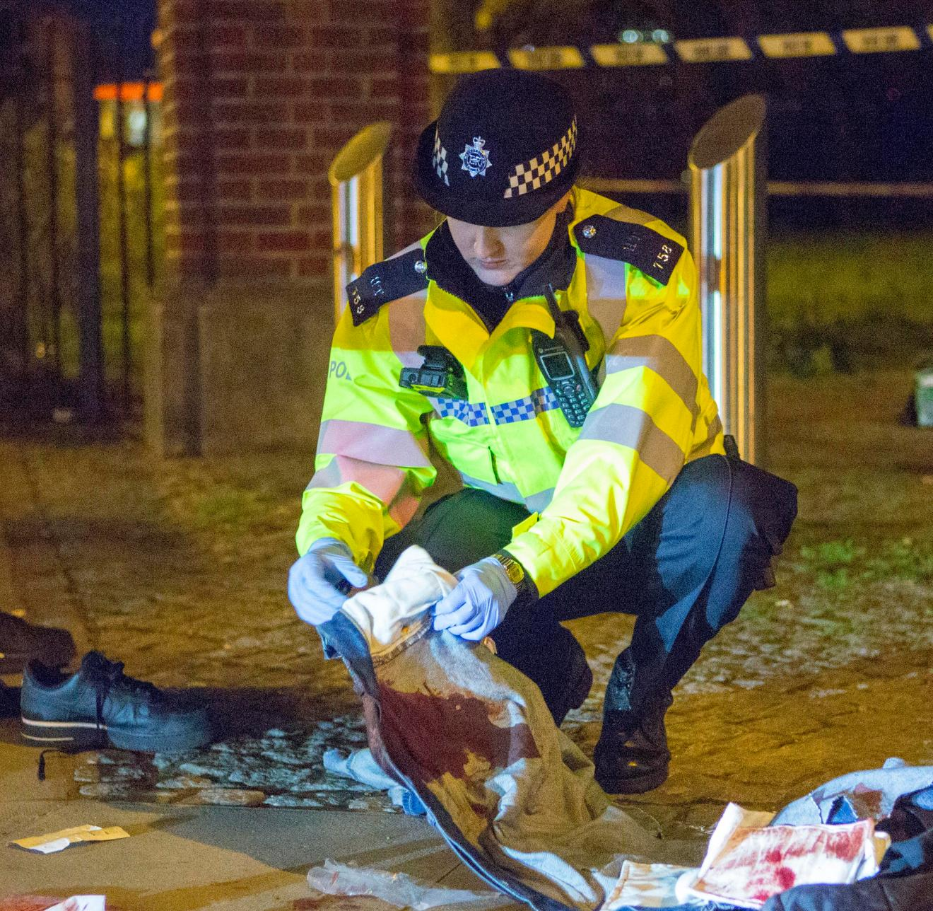 An officer picks up bloodied clothes at the scene of the attempted murder in Mile End