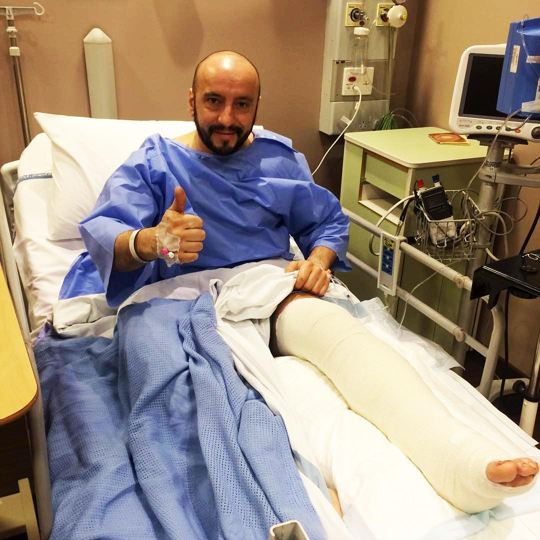 Ferrari mechanic Francesco Cigarini gives the thumbs up after having surgery after his horror accident