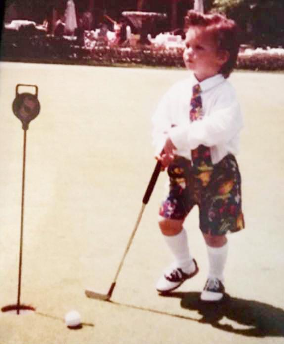 Reed with a golf club as a youngster