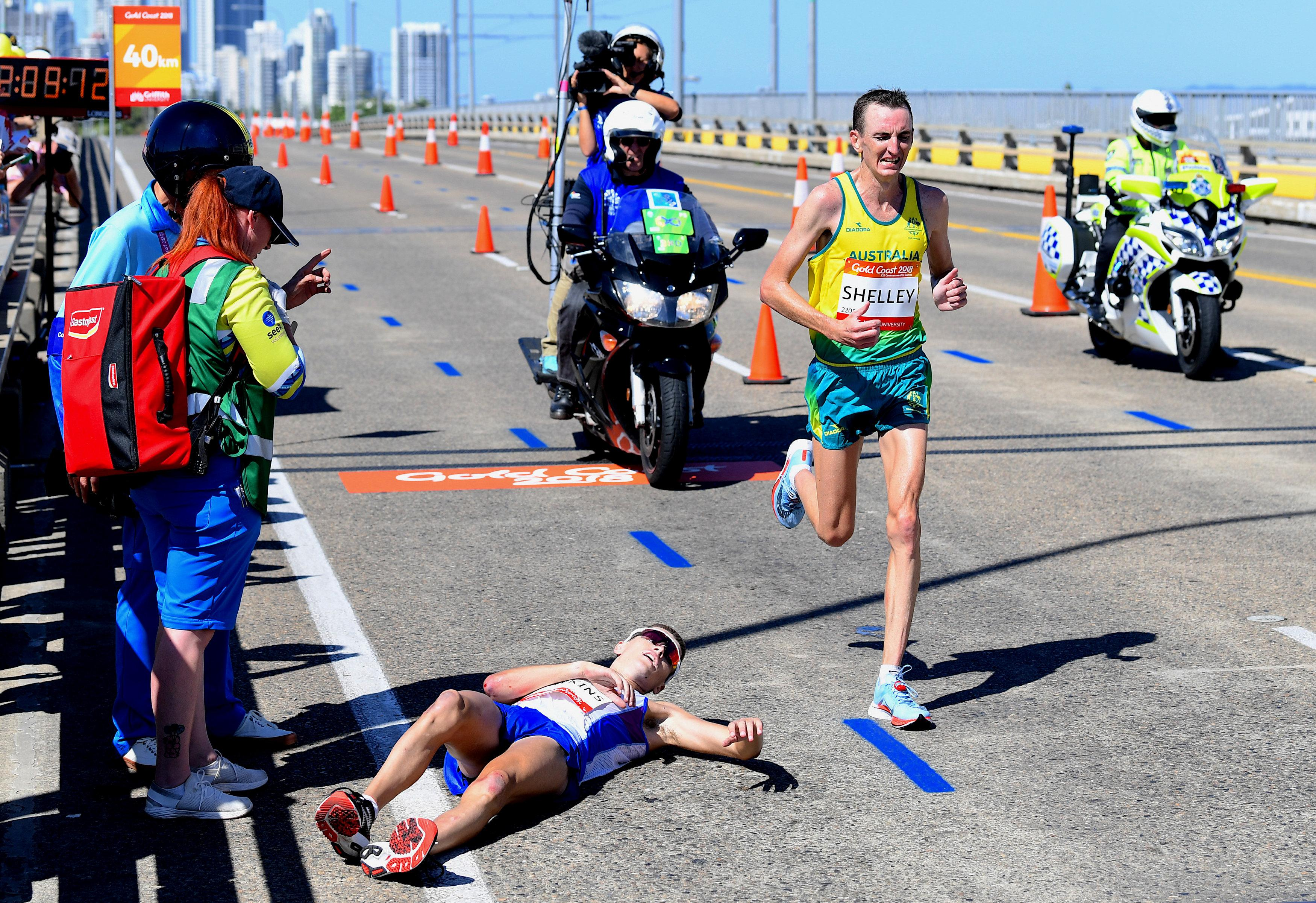Australian athlete Michael Shelley runs past fallen Callum Hawkins