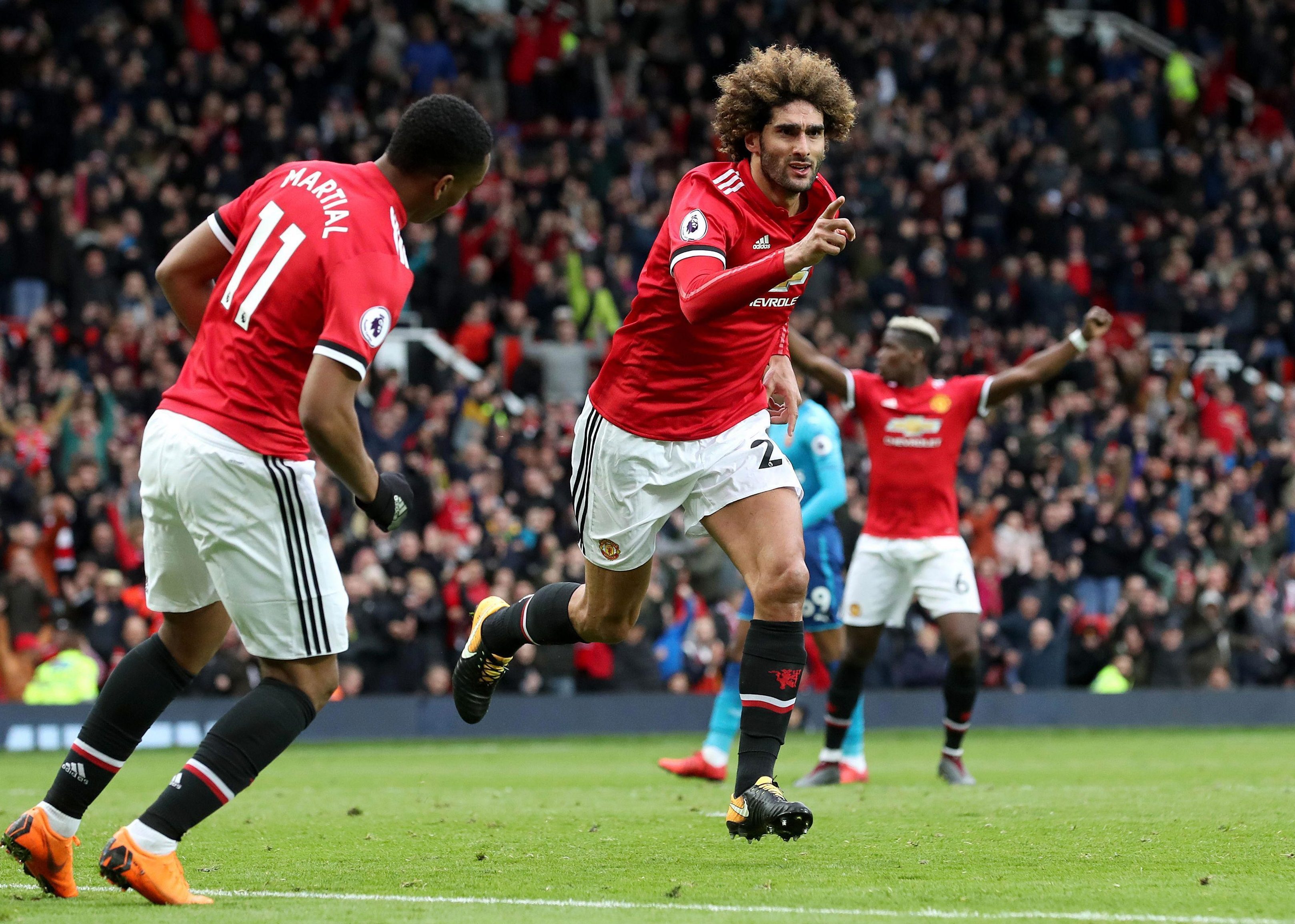 Marouane Fellaini celebrates his stoppage-time winner to tarnish what could be the last trip to Old Trafford as a manager for Arsene Wenger