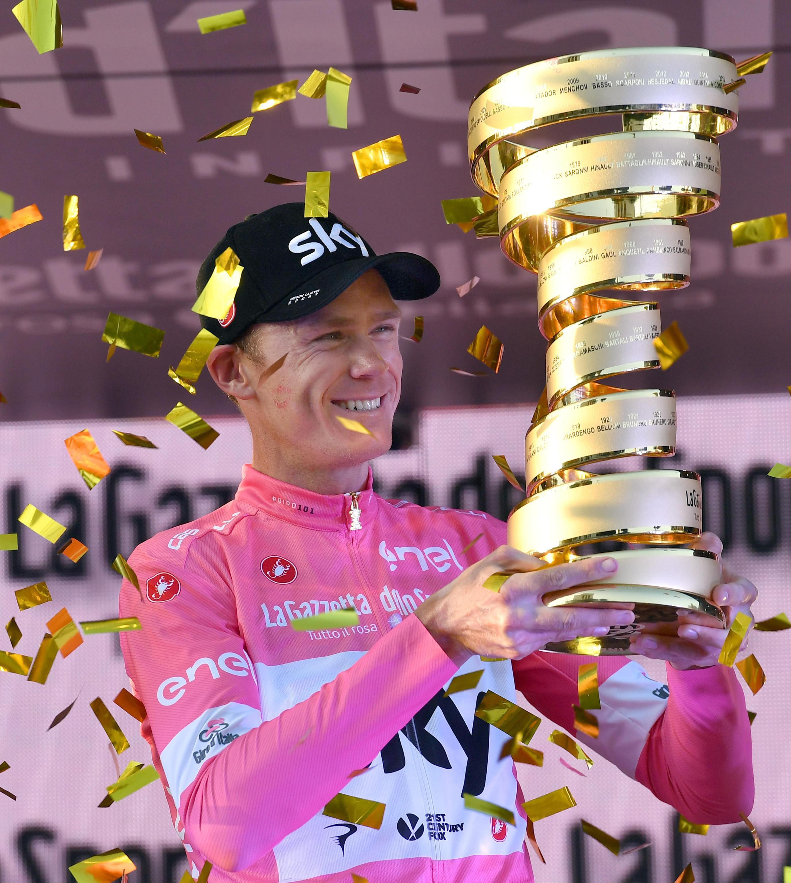 Froome celebrates as he is presented with the Giro trophy - his third Grand Tours in a row