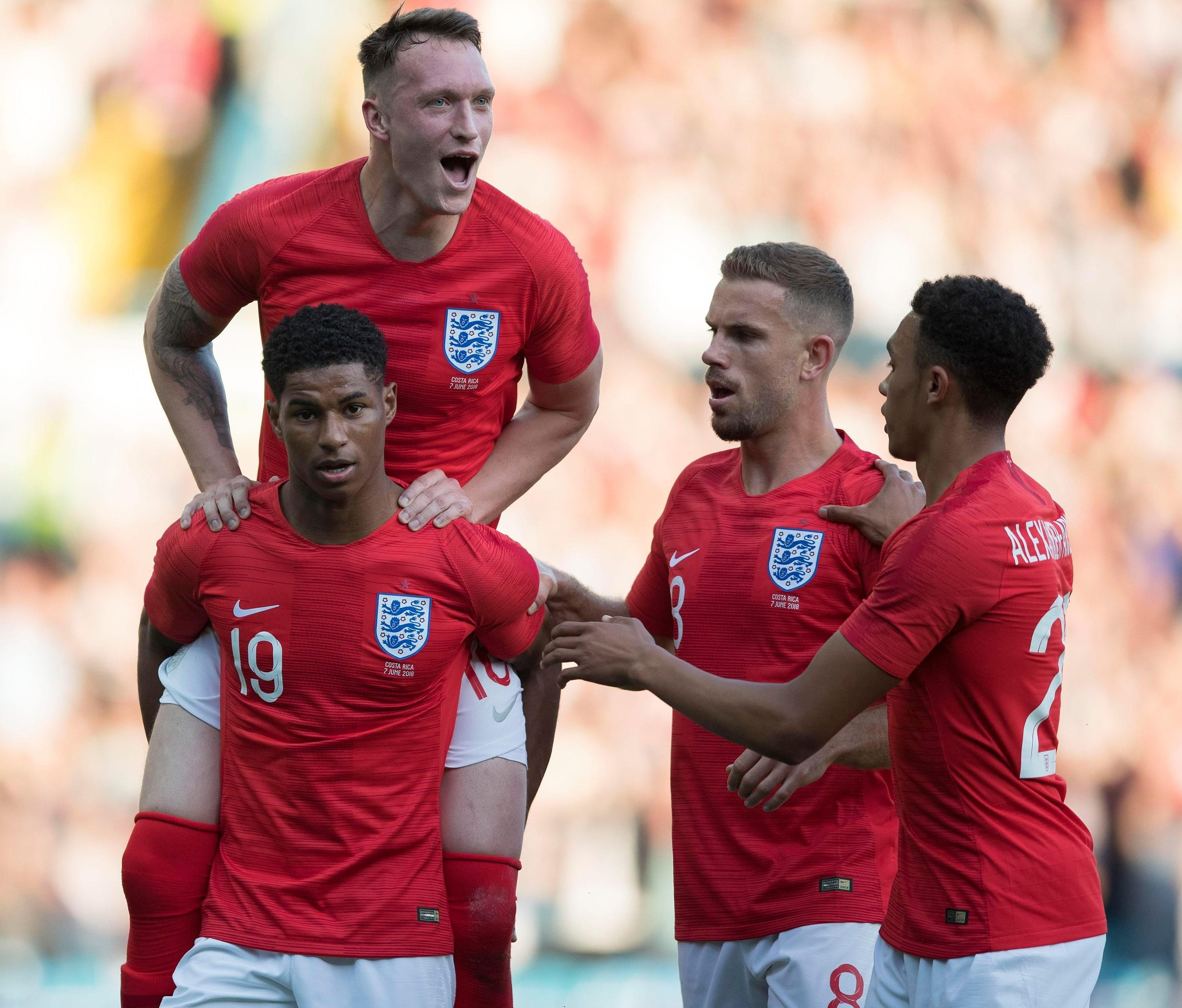Rashford is mobbed by his England team-mates after his stunning goal fired them ahead at Elland Road