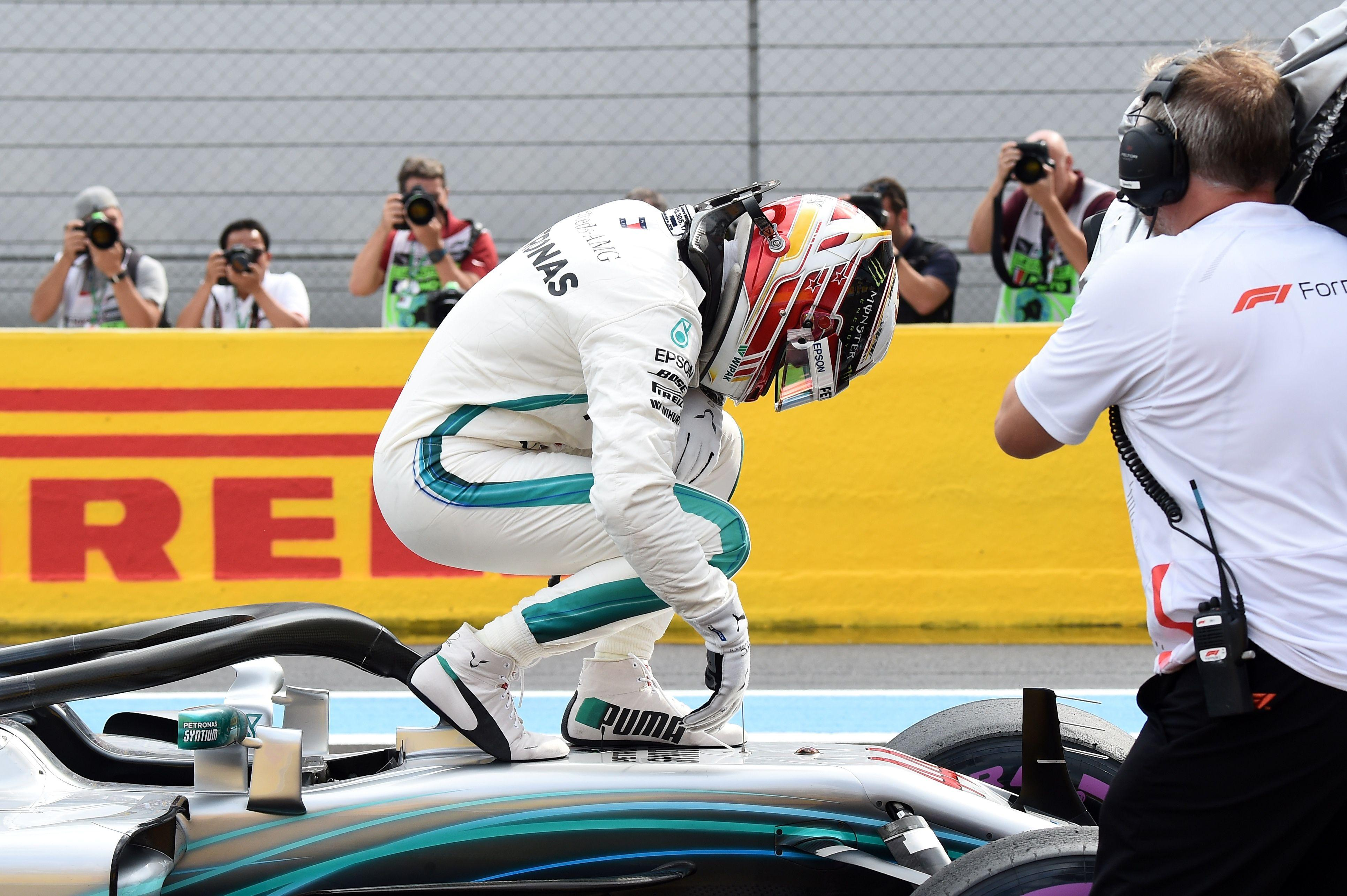 Lewis Hamilton stands on his car as he celebrates securing pole position