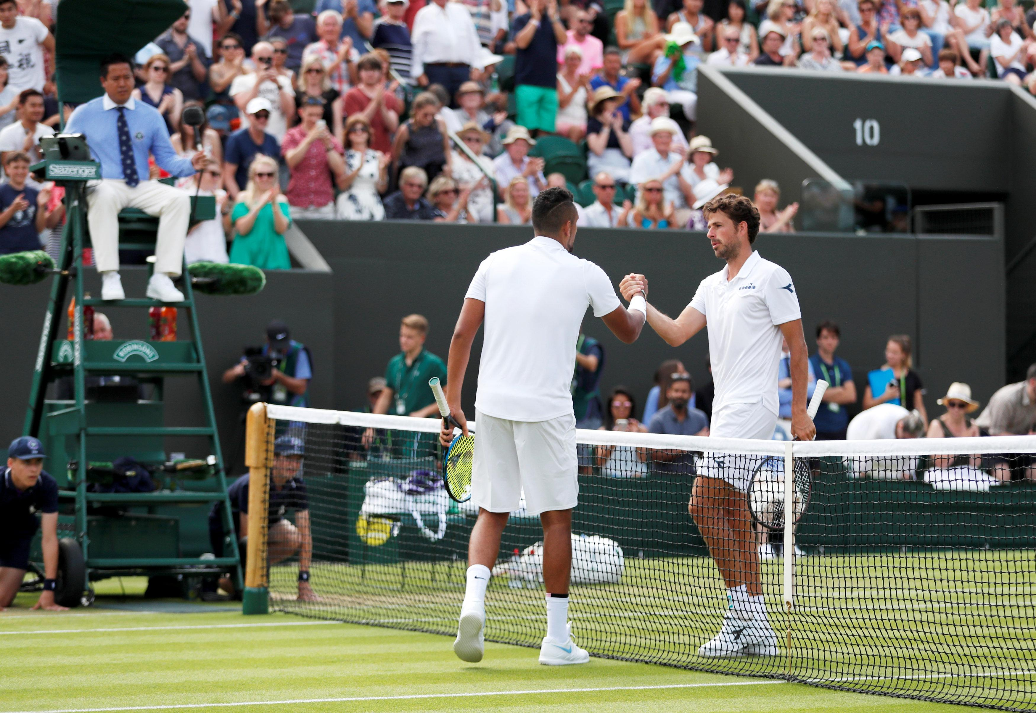 Kyrgios and Haase embrace at the end of their match on Court 3 at Wimbledon