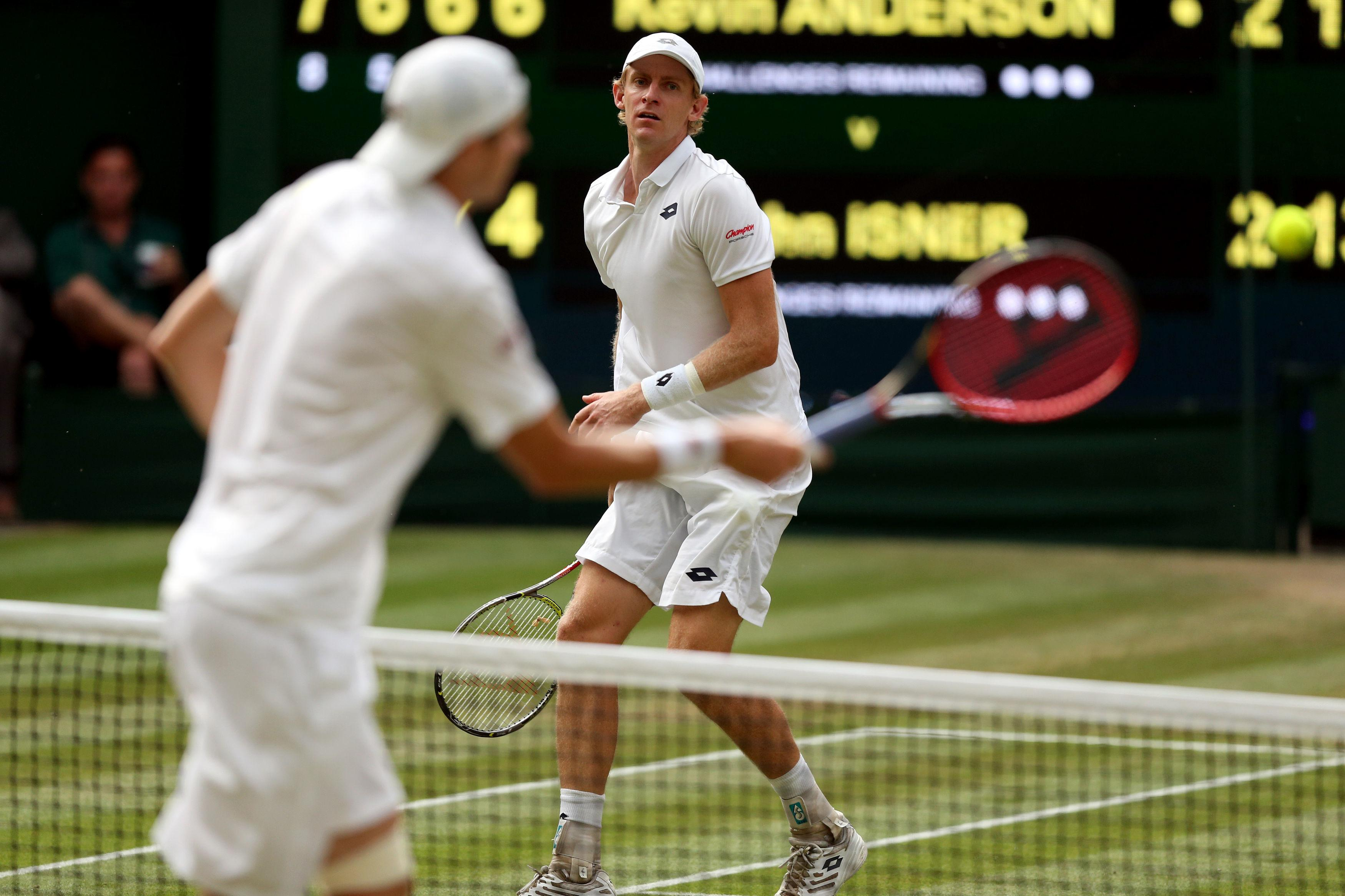 Kevin Anderson looks on as John Isner puts away a volley in their super-duel