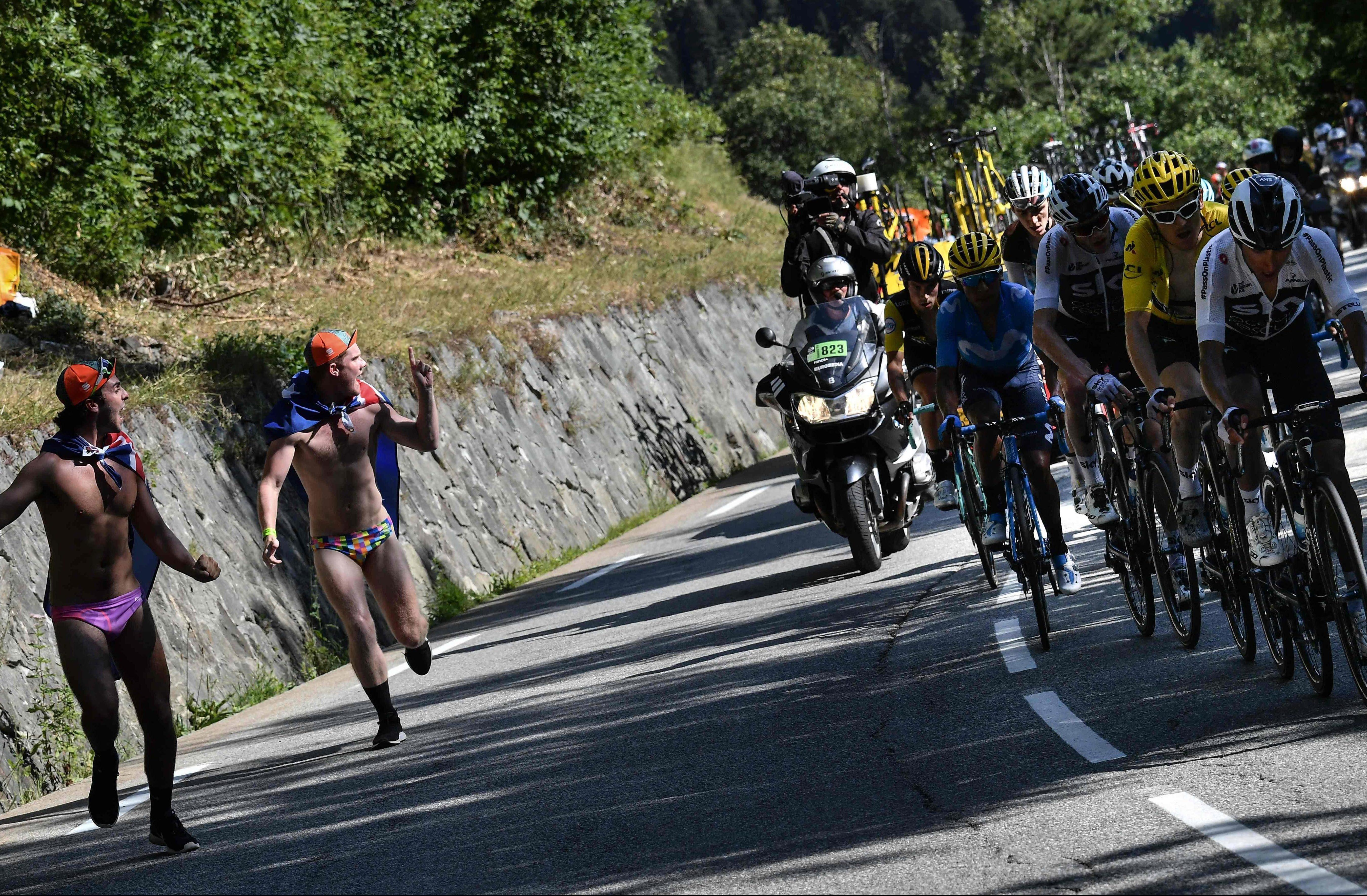 Fans run alongside, from right, Colombia's Egan Bernal, Geraint Thomas, Chris Froome, France's Romain Bardet (rear) and Colombia's Nairo Quintana