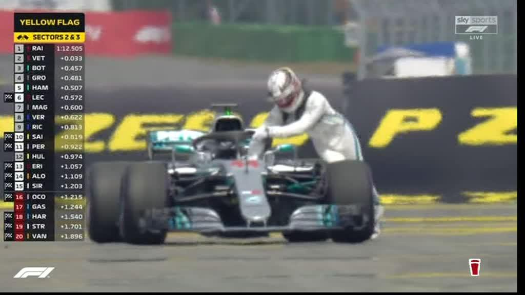 Lewis Hamilton attempts to push his stricken Mercedes back to the pits after breaking down in qualifying