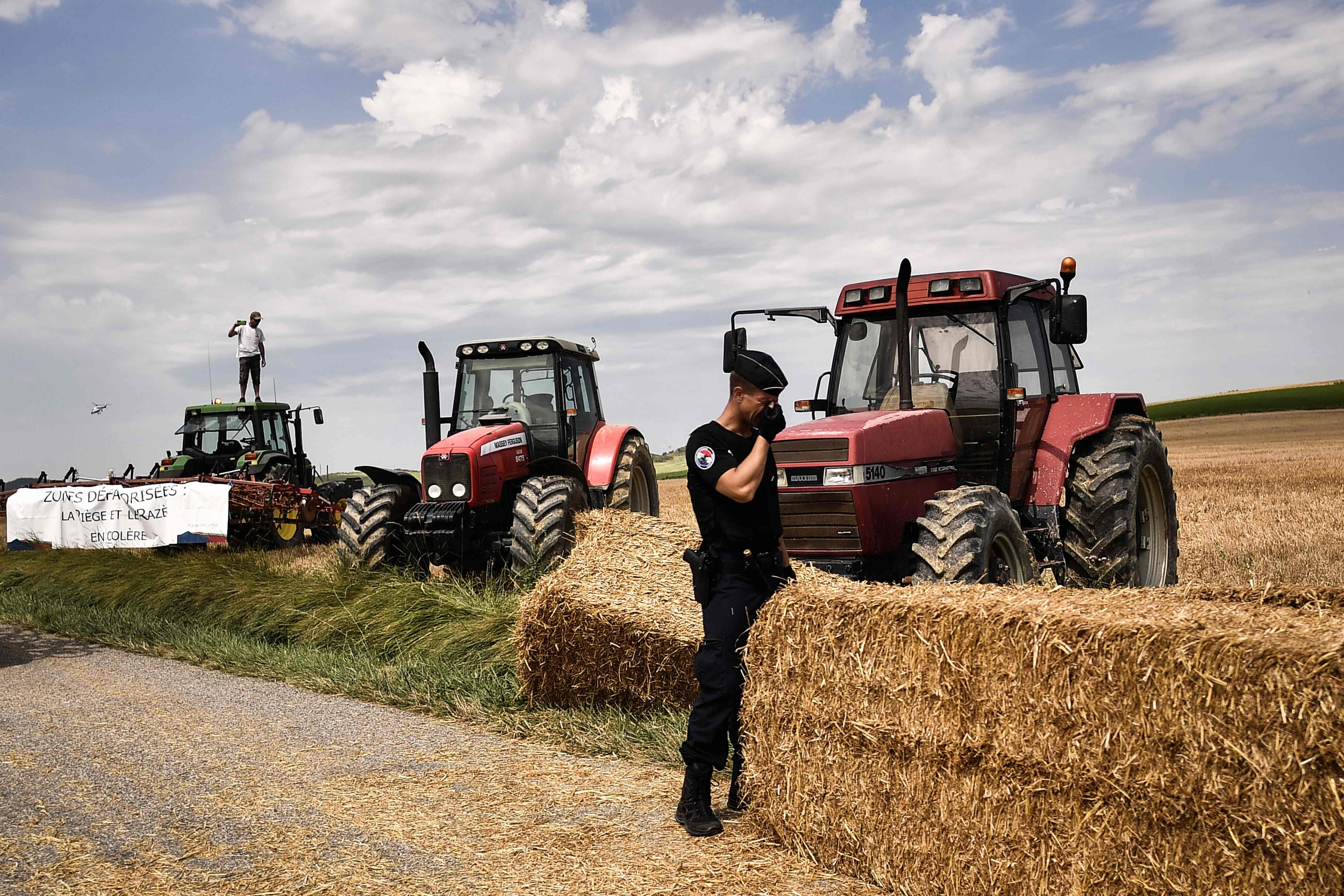 A policeman covers his face in front of the tractors that loaded bales of hay into the road at the Tour de France