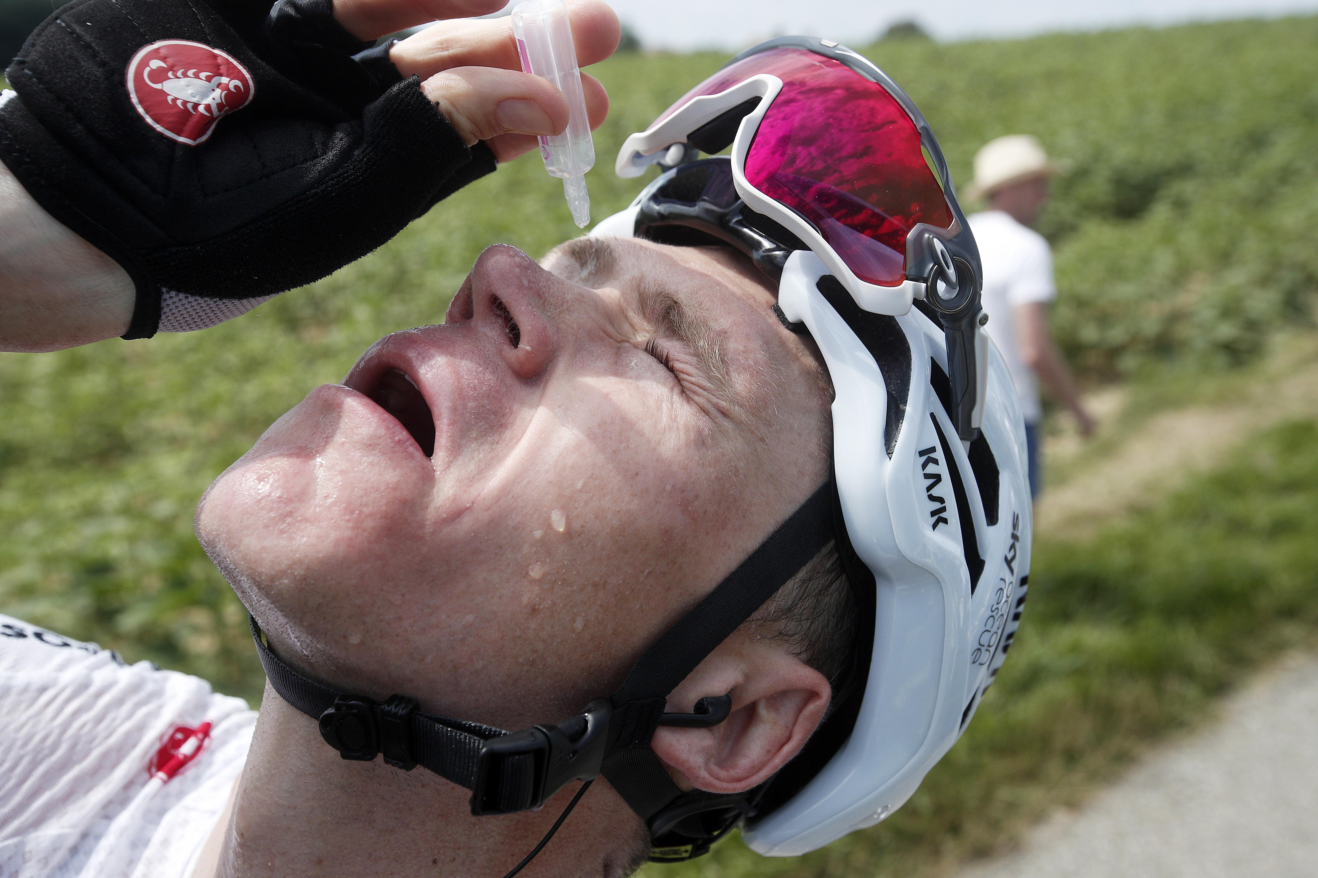 Chris Froome puts eye drops in his eyes after being affected by the gas