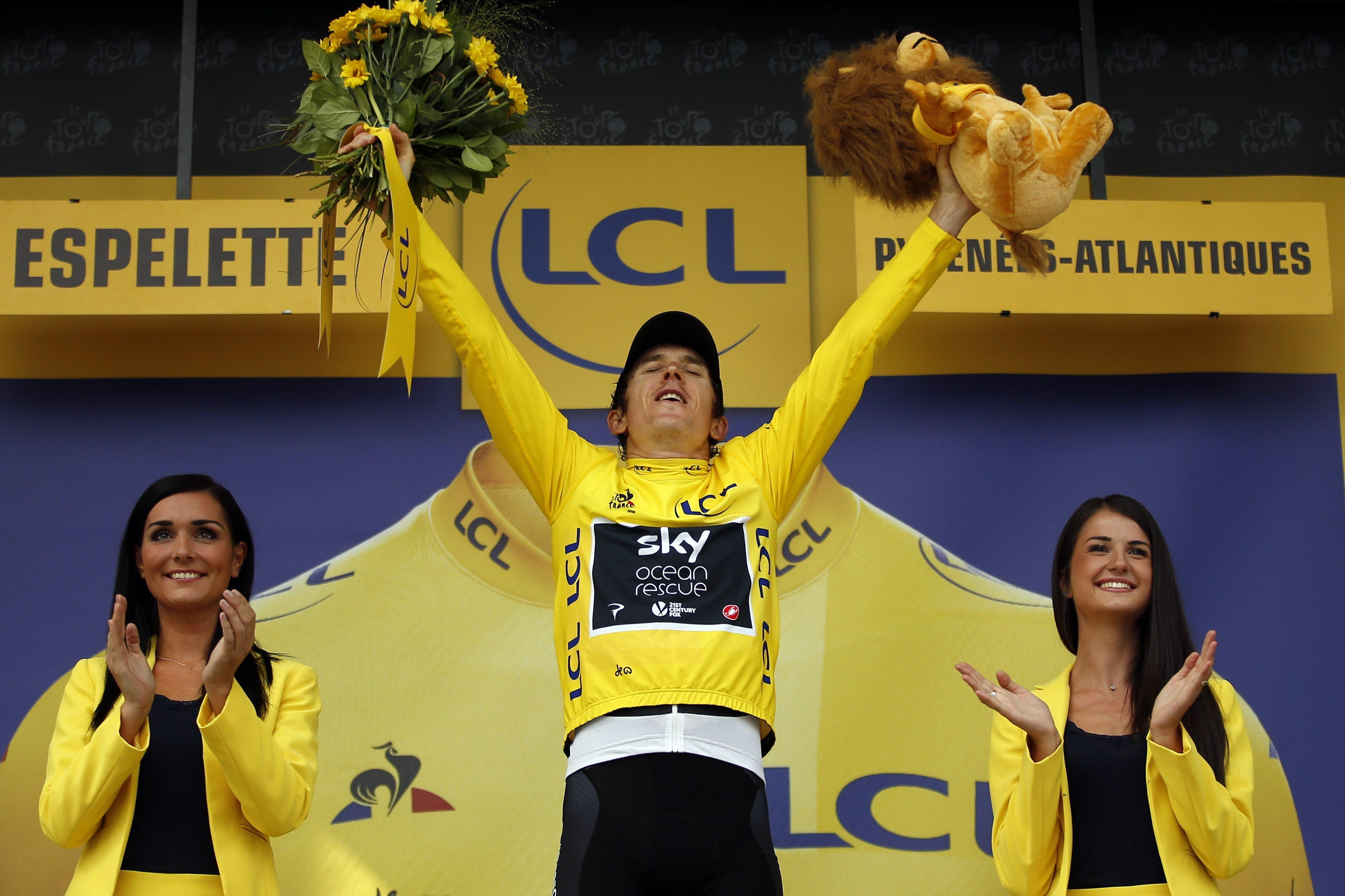 Geraint Thomas celebrates after retaining the yellow jacket after the 20th stage