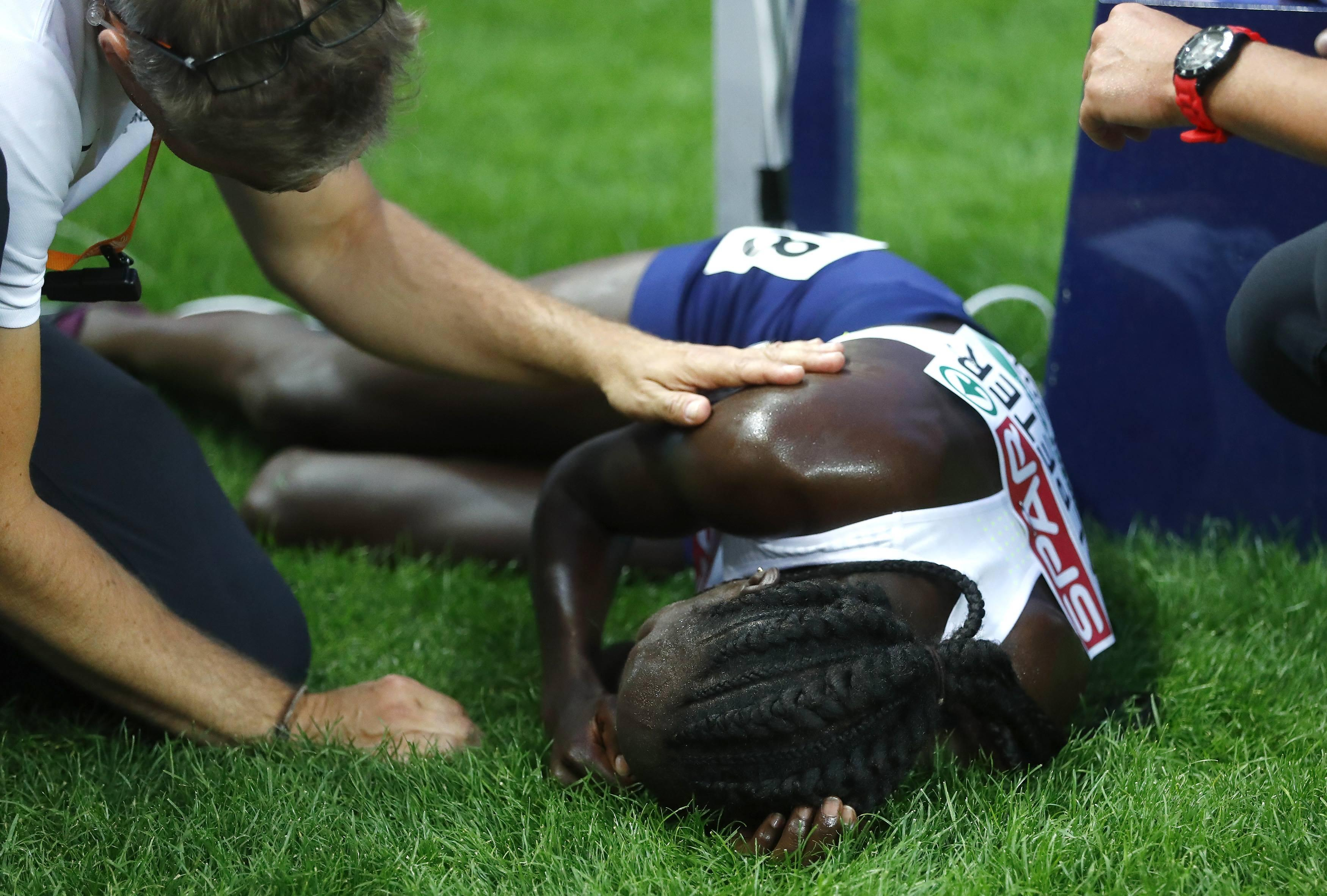 Lonah Salpeter weeps on the grass after finishing fourth