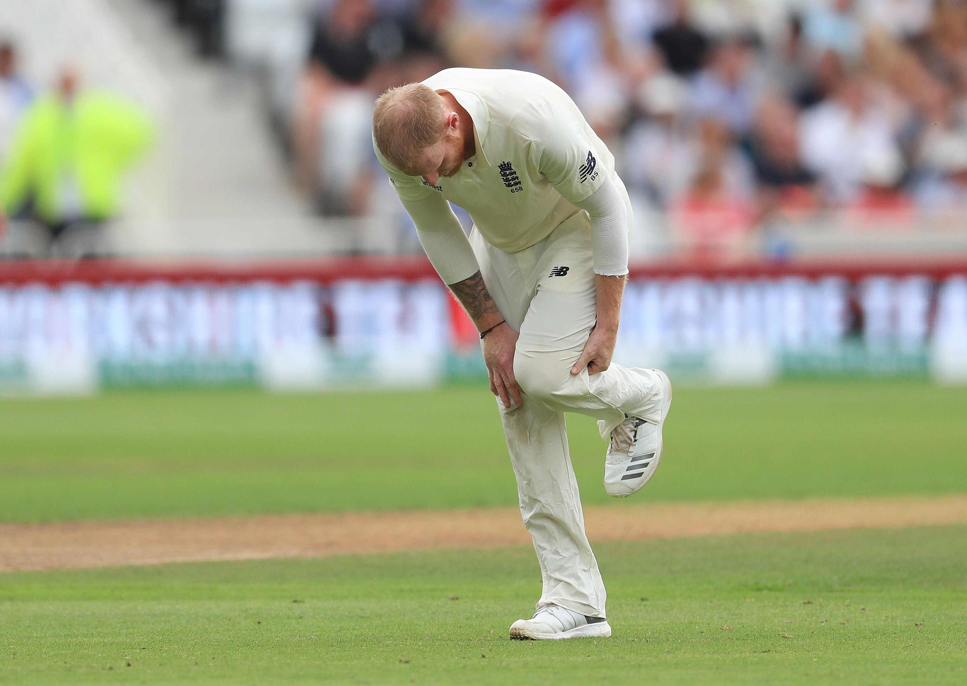 Ben Stokes holds his knee in the field as England toil