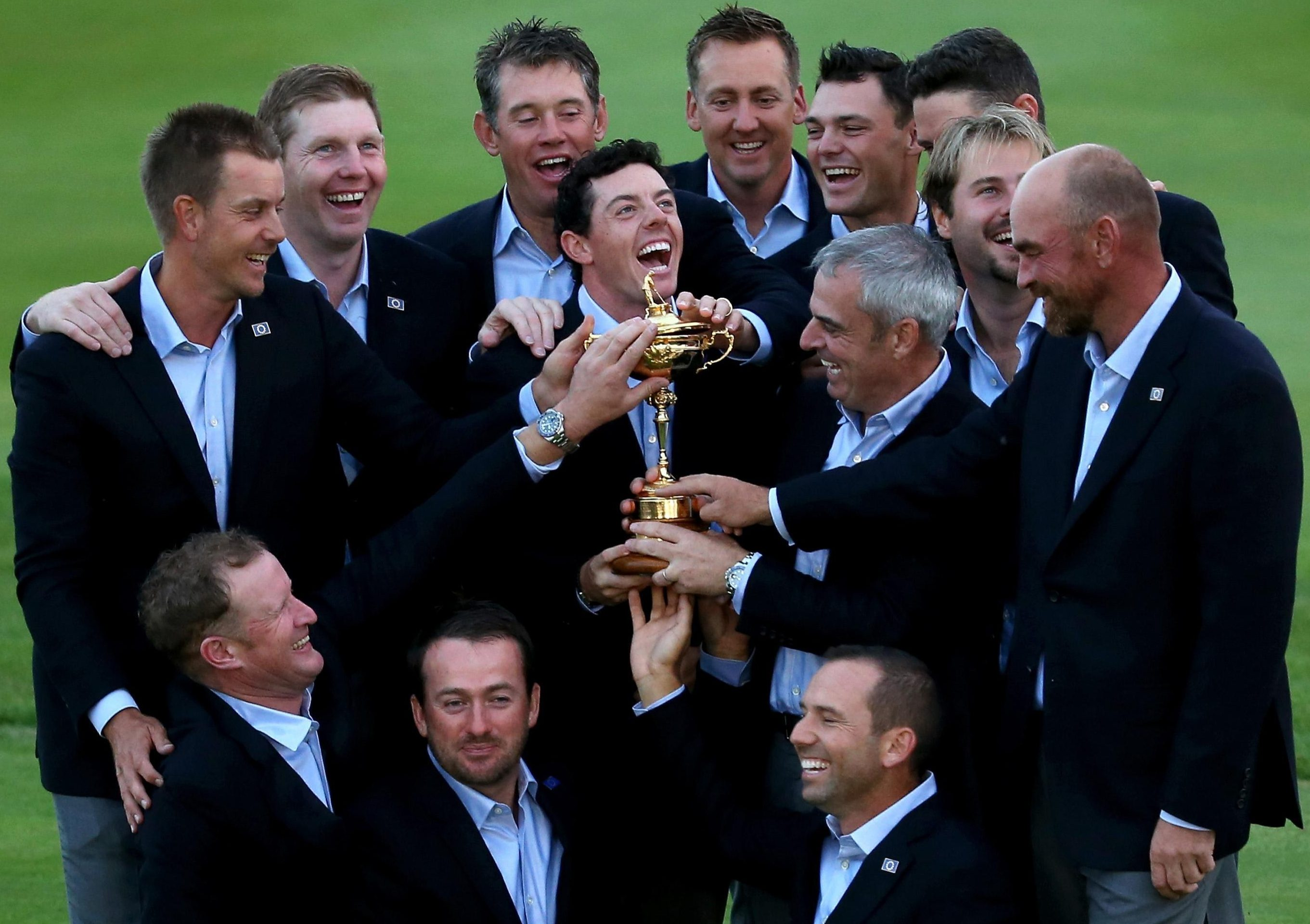Europe team captain Paul McGinley and Rory McIlroy with the Ryder Cup trophy as teammates join in the celebrations after victory at Gleneagles in 2014