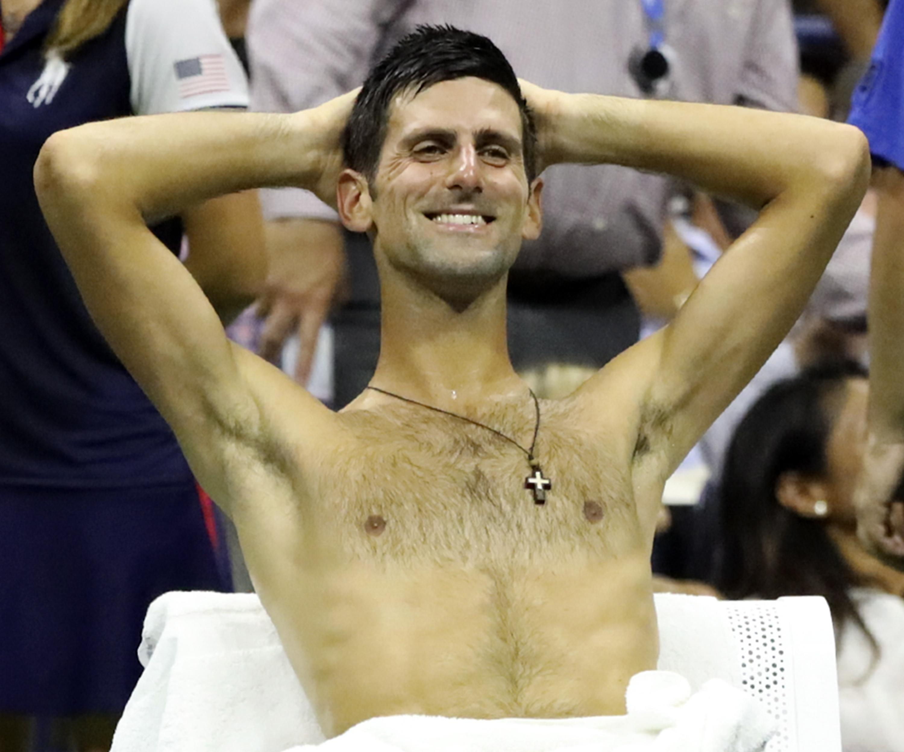 Novak Djokovic cools down with his shirt off at the US Open