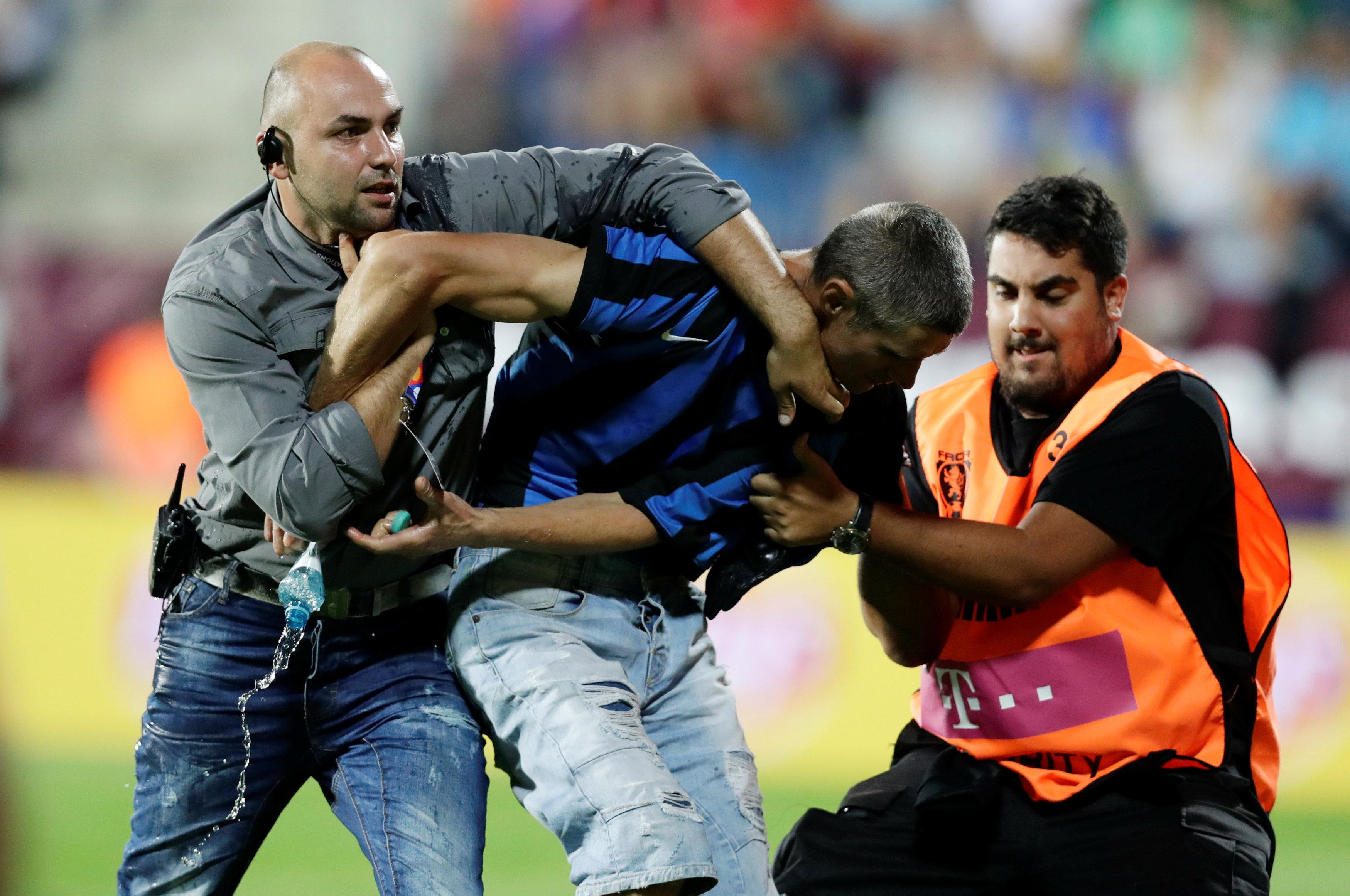 Security guards apprehend a pitch invader after Thursday night's game