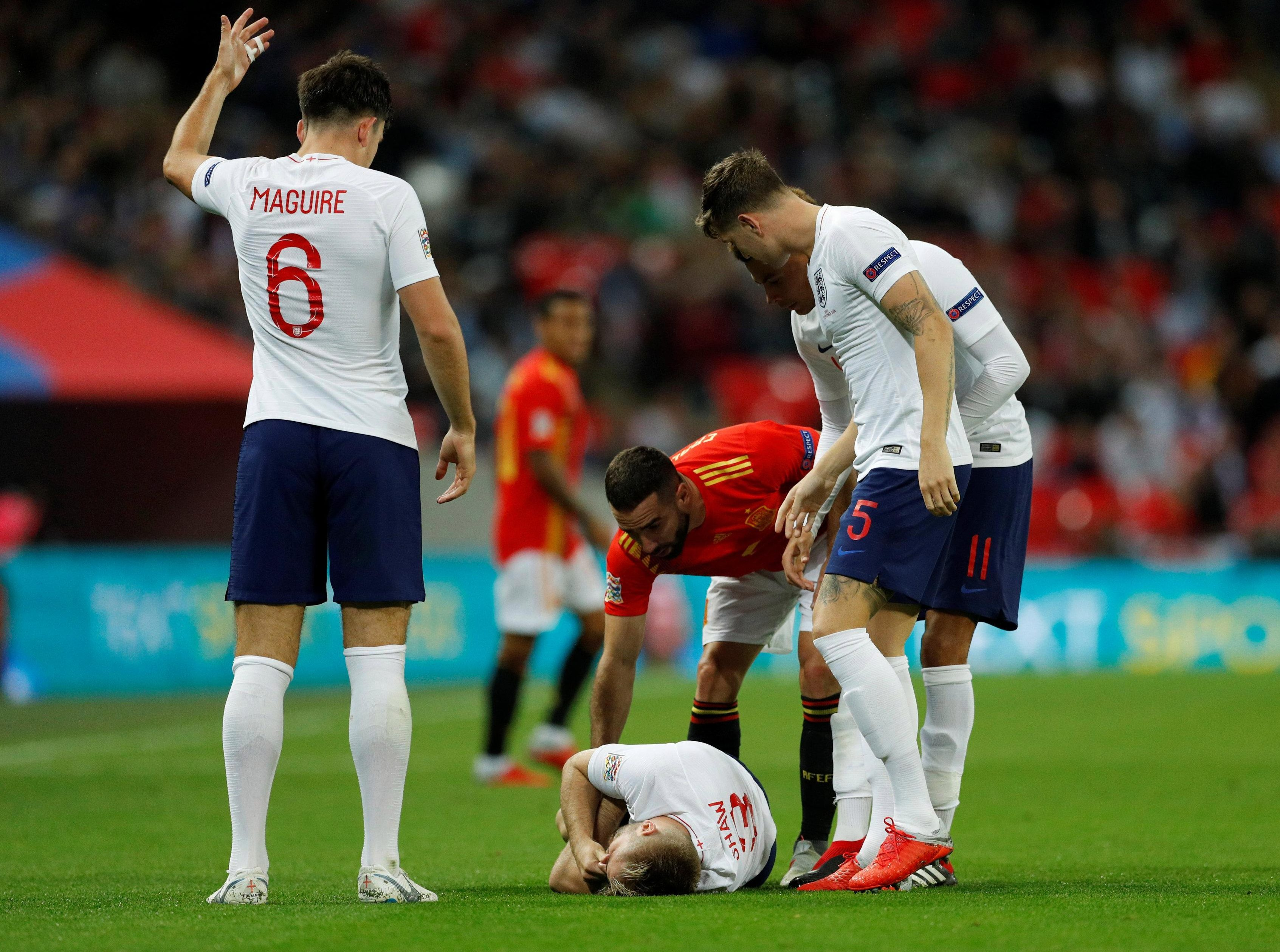 England players and Dani Carvajal show their concern as Luke Shaw is grounded