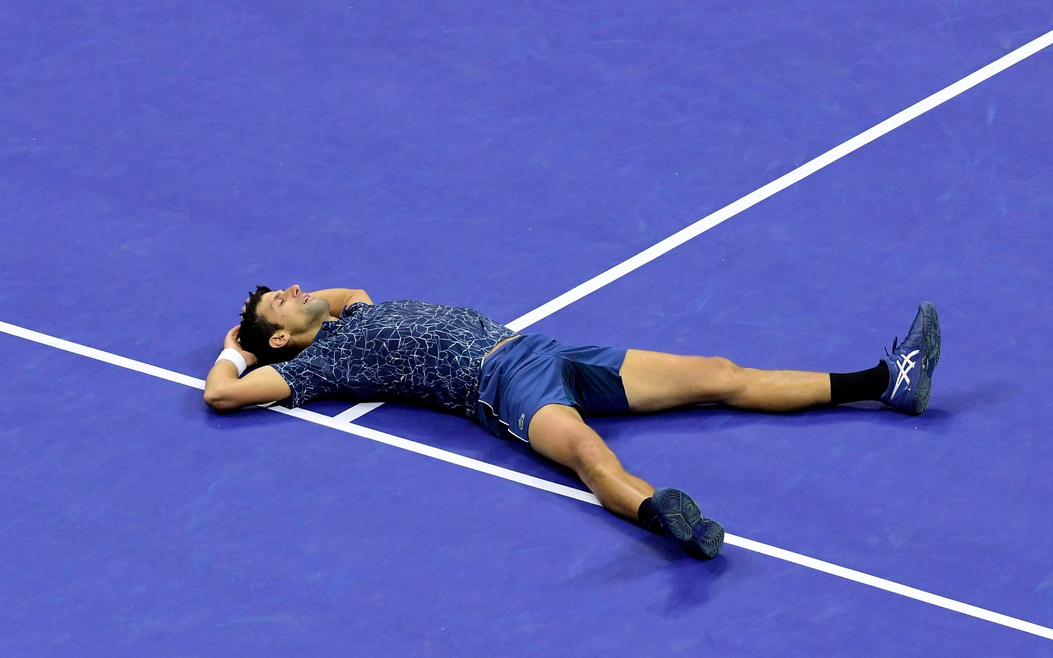 Novak Djokovic lays on the ground in triumph after winning the US Open